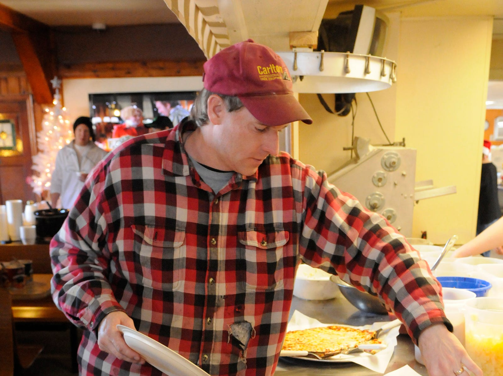 Jeremy Girtz, Freedom, comes back for a second helping of pizza at Charlie's Pizza in Little Falls Tuesday, Dec. 25, 2012. Owner Charlie Peterka opened his restaurant and served free pizza to anyone who did not have holiday plans.
