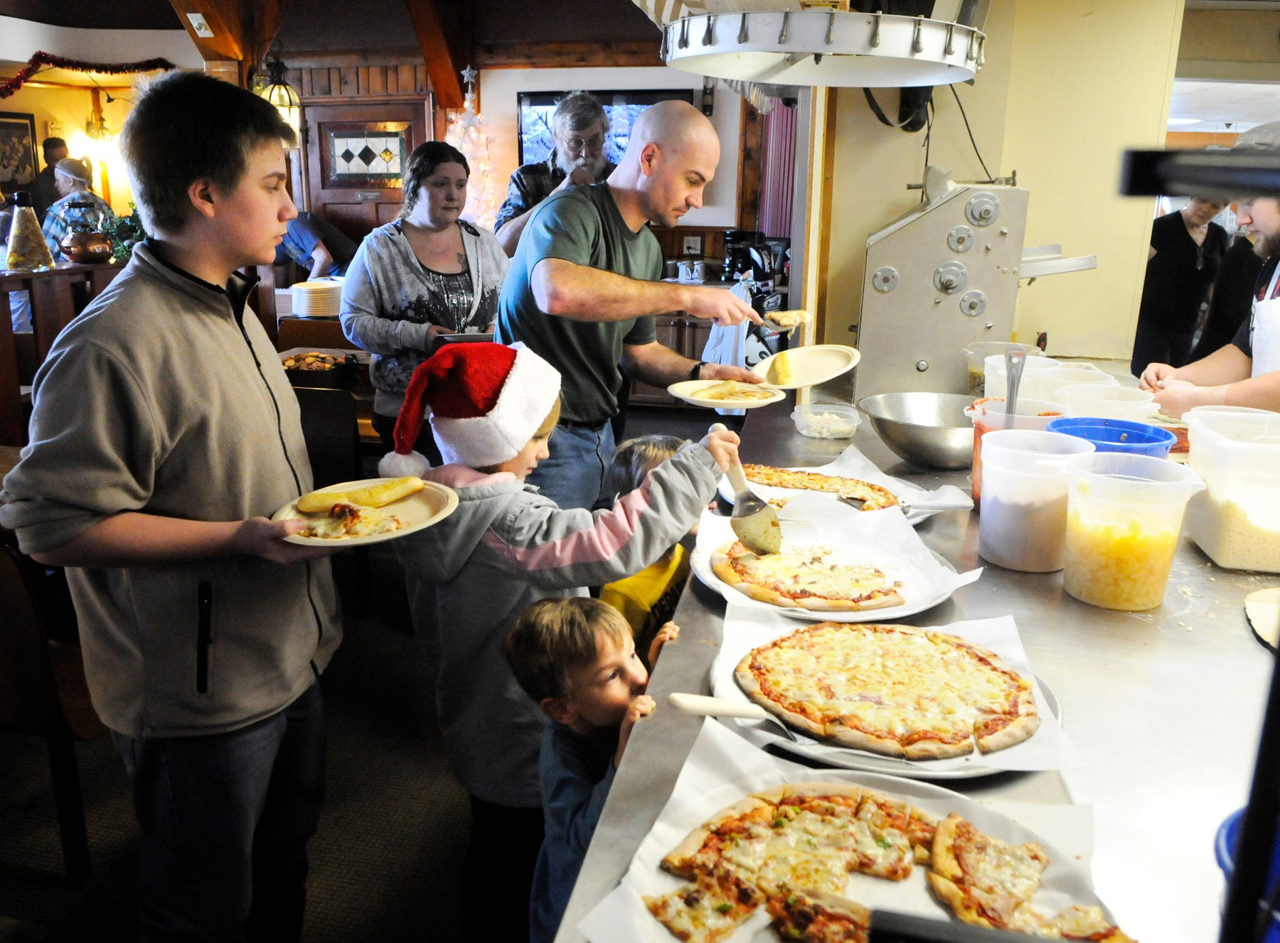 People get pizza and soup at Charlie's Pizza in Little Falls Tuesday, Dec. 25, 2012. Owner Charlie Peterka opened his restaurant and served free pizza to anyone who did not have holiday plans
