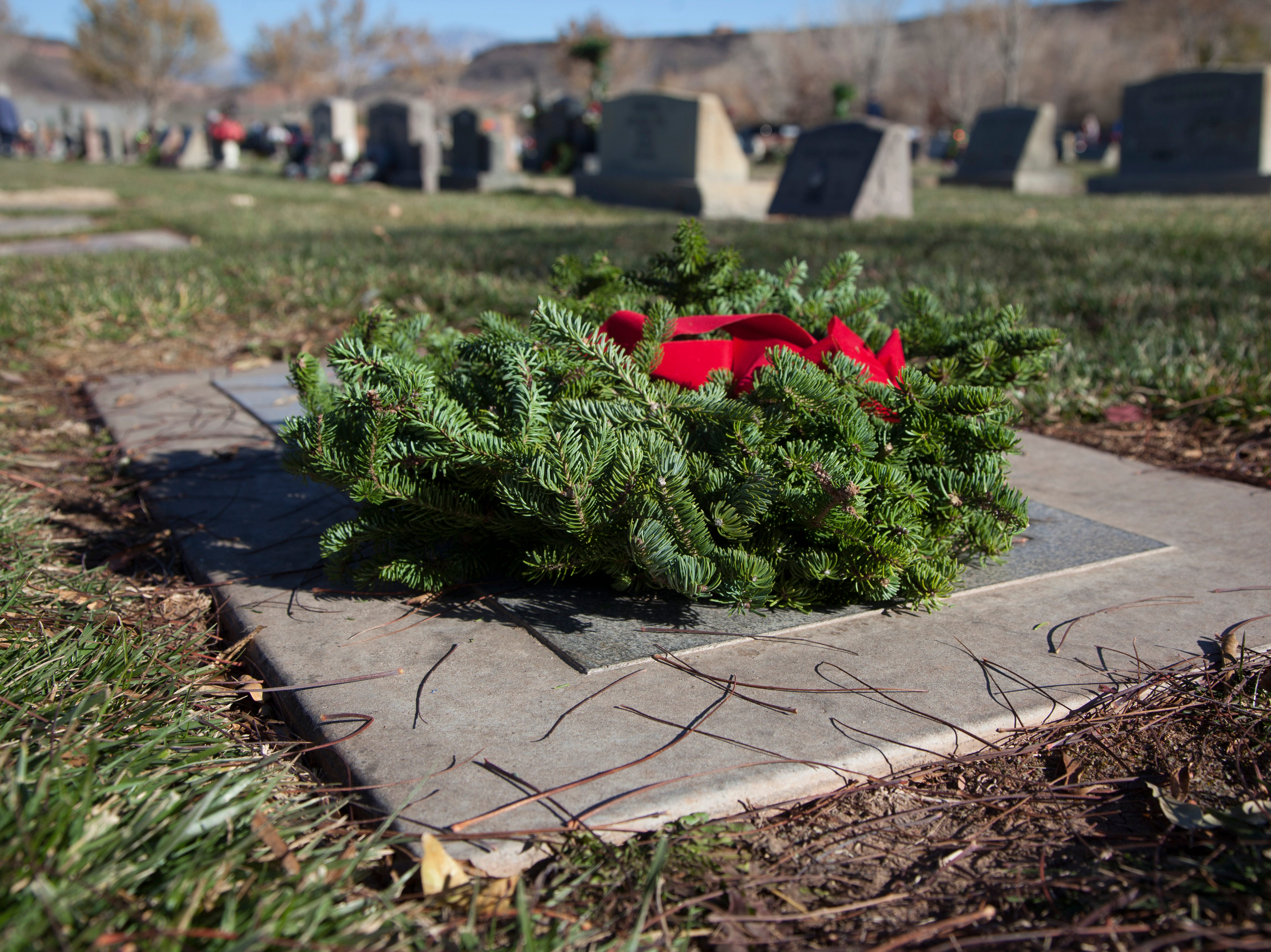 Community members place wreaths on the headstones of veterans at the Tonaquint Cemetery as part of the Wreaths Across America Saturday, Dec. 15, 2018.