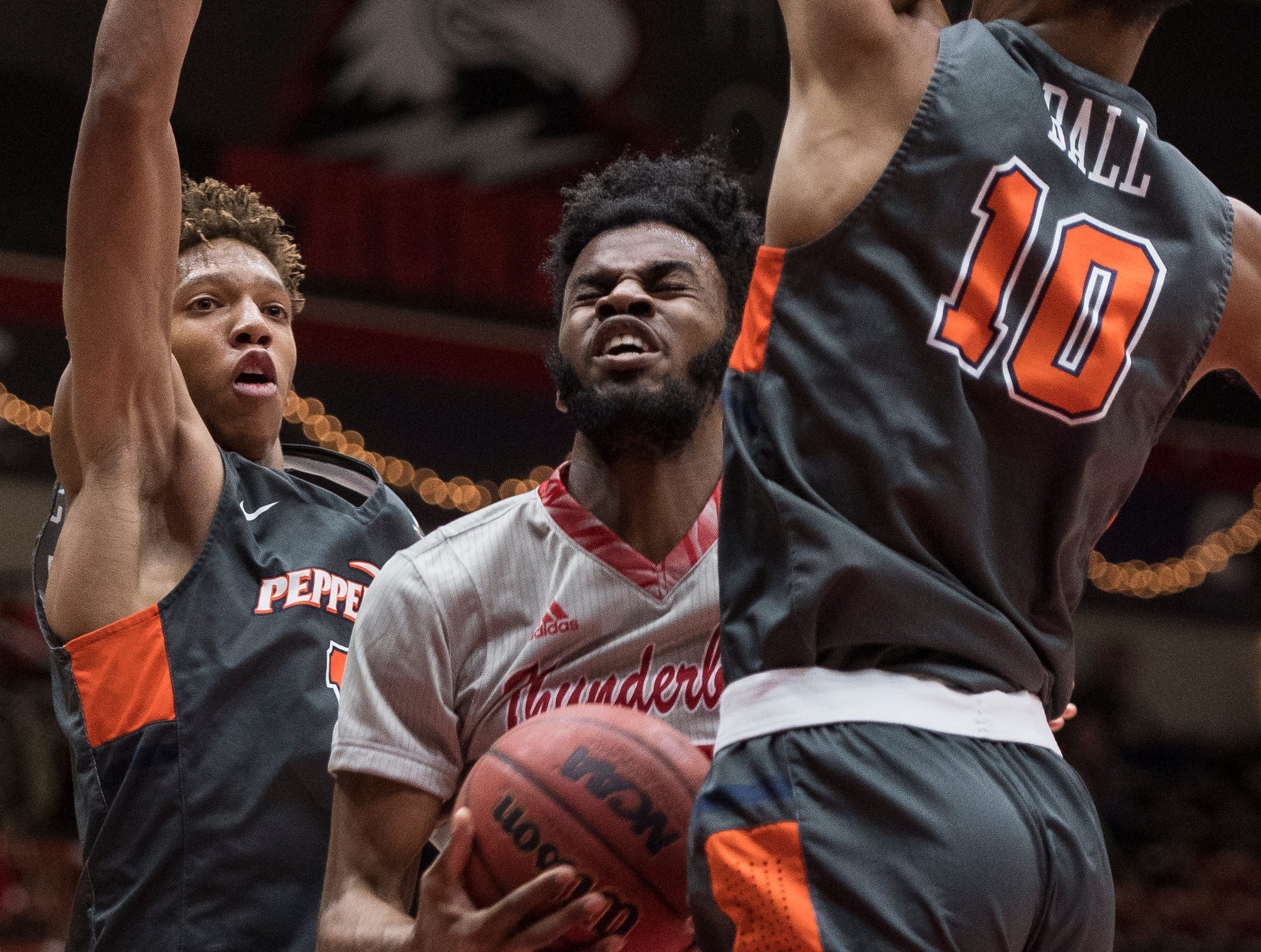 Southern Utah University junior Cameron Oluyitan (23) squeezes through traffic for an equalizing basket late in the game against Pepperdine University in the America First Event Center Saturday, December 15, 2018. SUU won in overtime, 78-69.