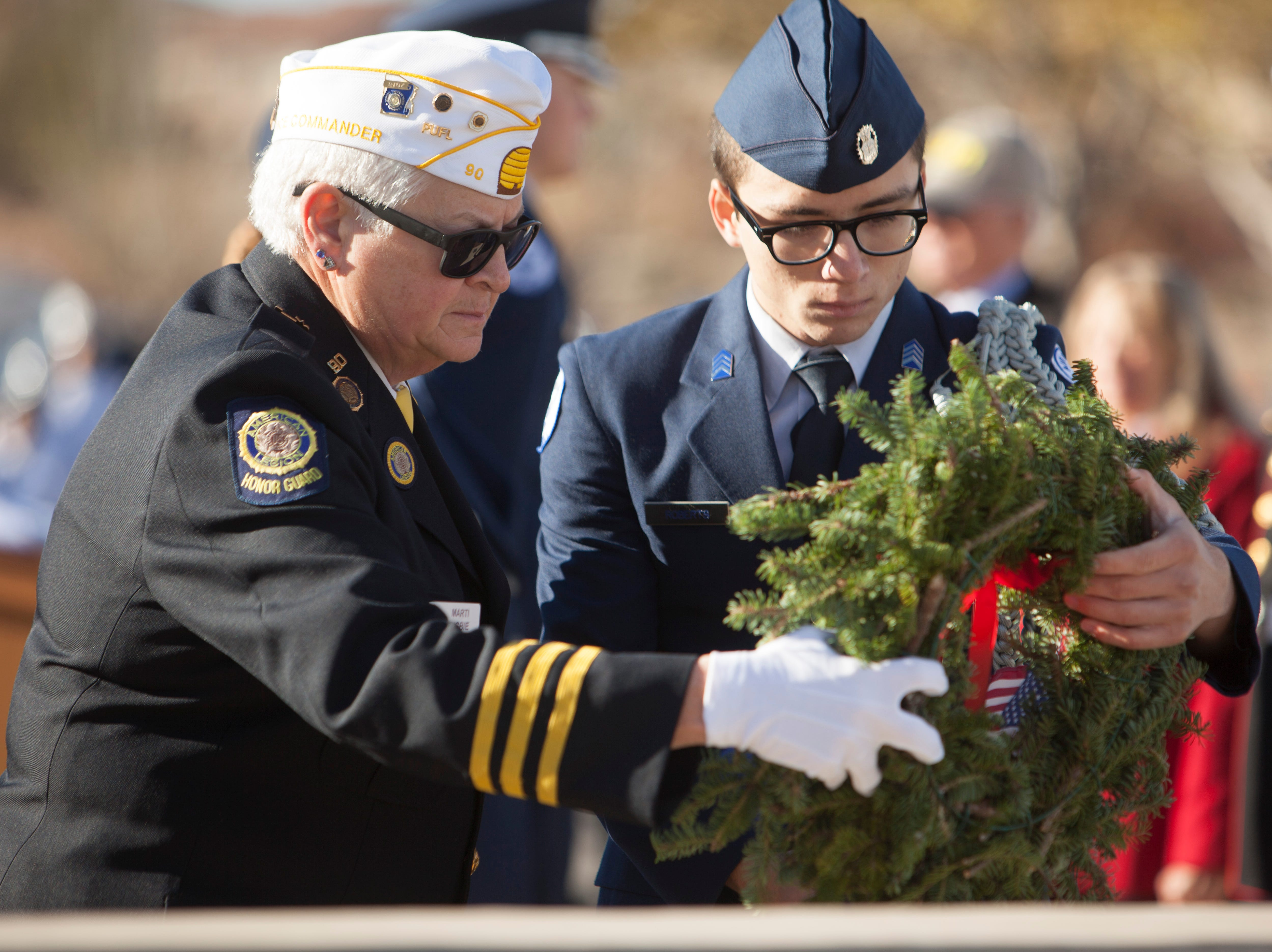 Marti Bigbie, commander of American Legion Post 90, and a member of the Dixie High Air Force JROTC place a wreath at Tonaquint Cemetery in St. George as part of the Wreaths Across America event Saturday, Dec. 15, 2018.