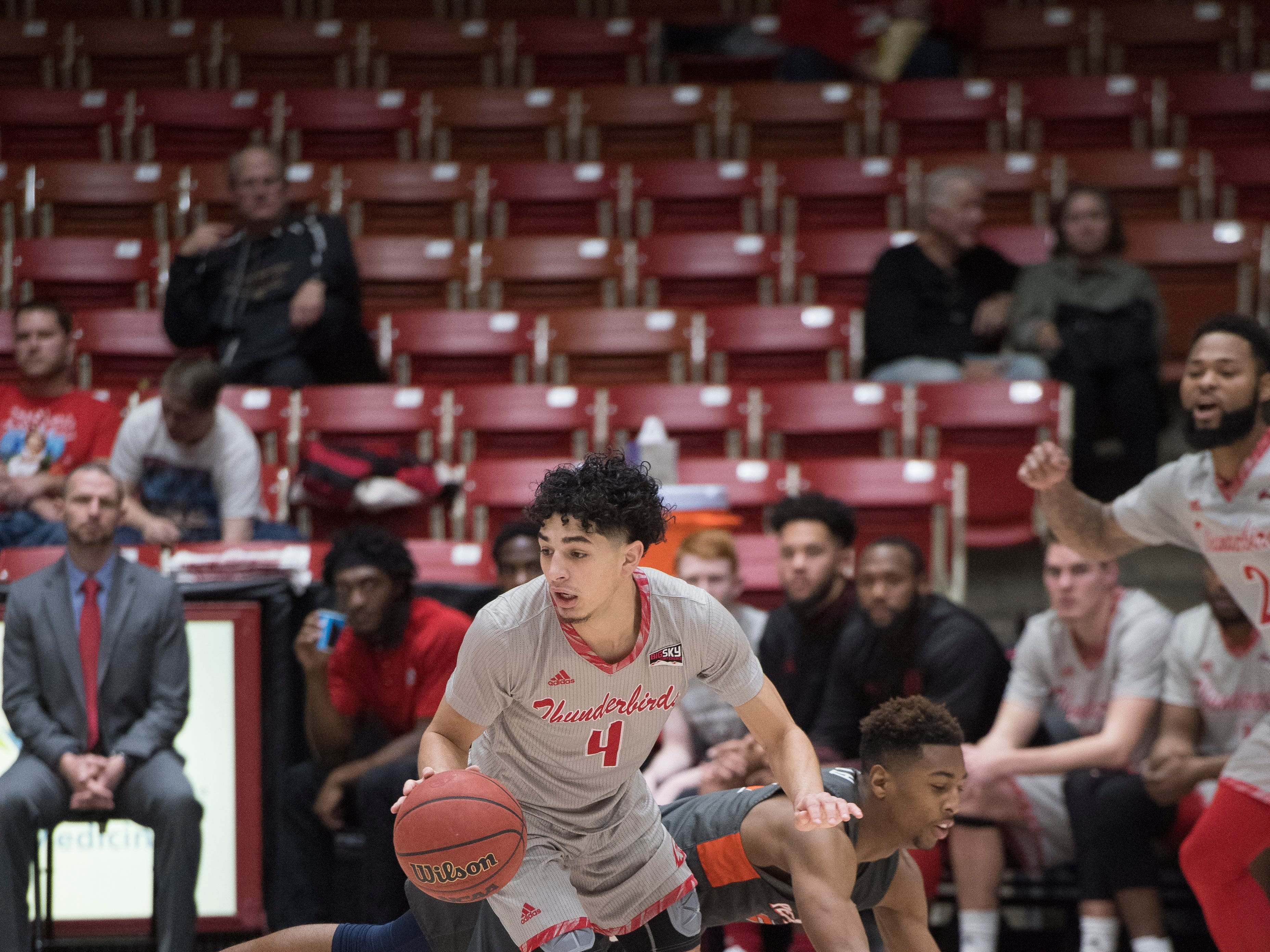 Southern Utah University sophomore Dre Marin (4) jukes a Pepperdine defender in the America First Event Center Saturday, December 15, 2018. SUU won in overtime, 78-69.