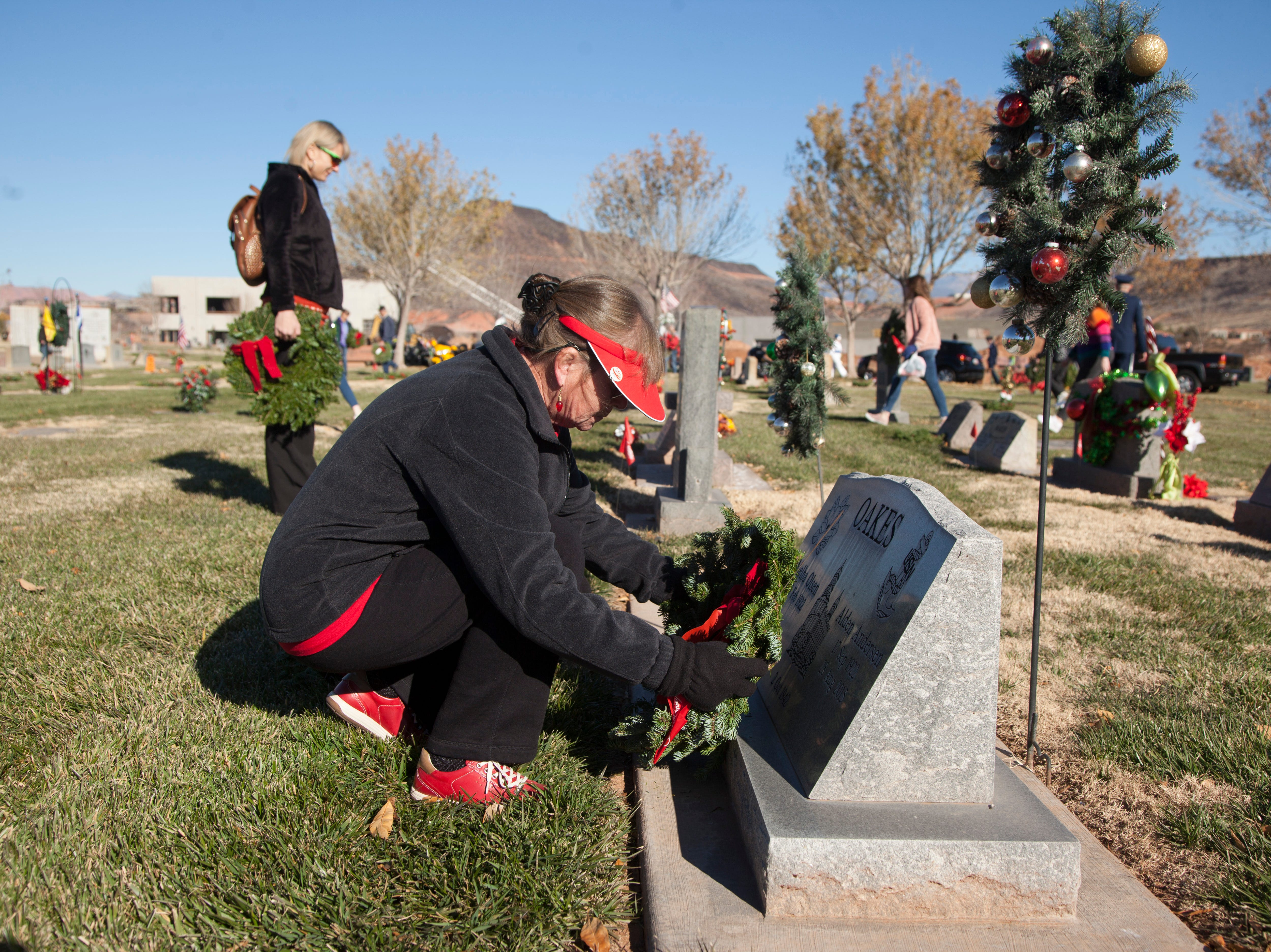 Community members place wreaths on the headstones of veterans at the Tonaquint Cemetery in St. George as part of the nationwide Wreaths Across America event on Dec. 15, 2018. The Color Country Chapter of the Daughters of the American Revolution organized this year's effort to place more than 1,800 wreaths at three Southern Utah cemeteries.