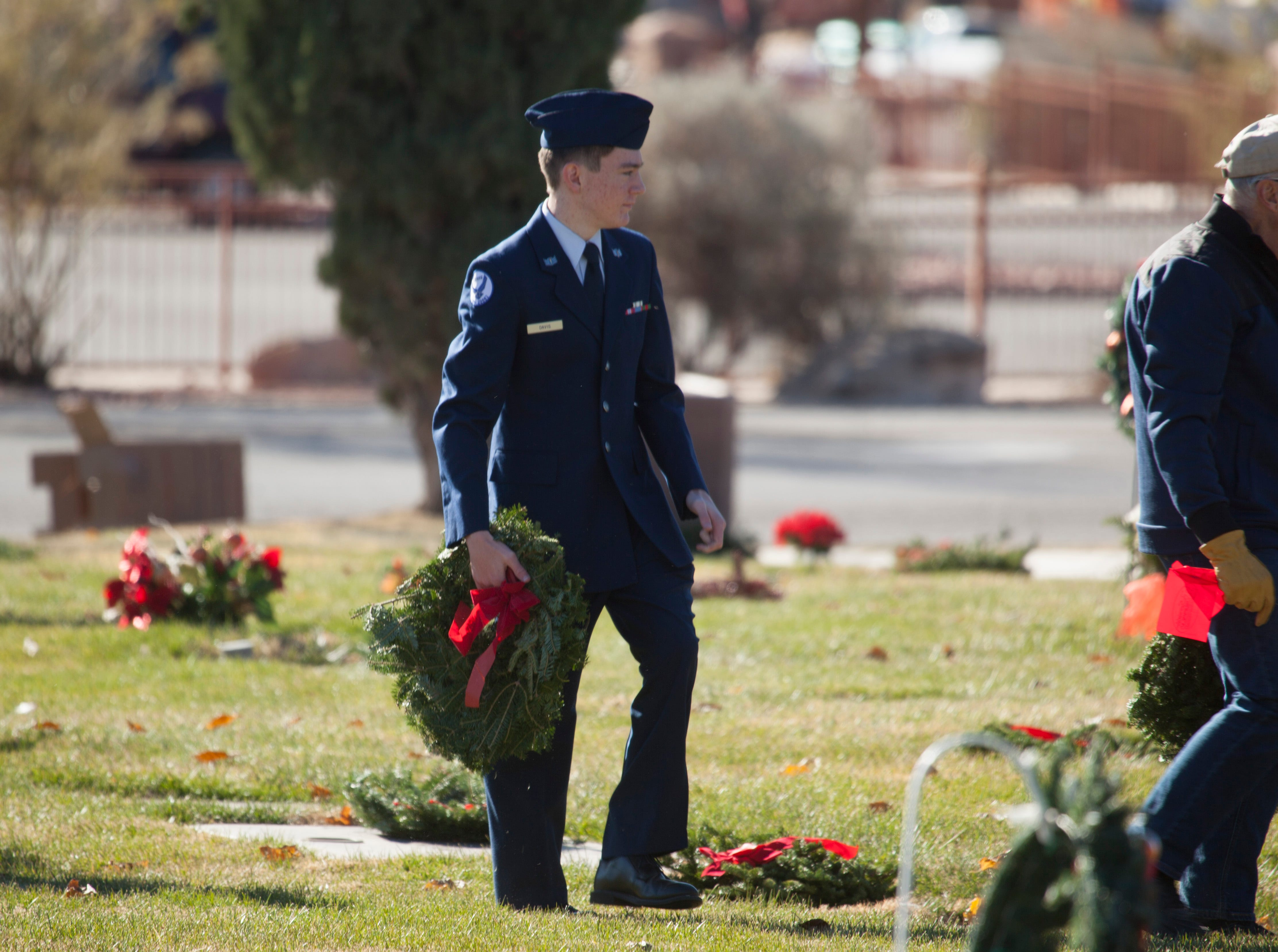 Community members place wreaths on the headstones of veterans at the St. George Cemetery as part of the Wreaths Across America Saturday, Dec. 15, 2018.