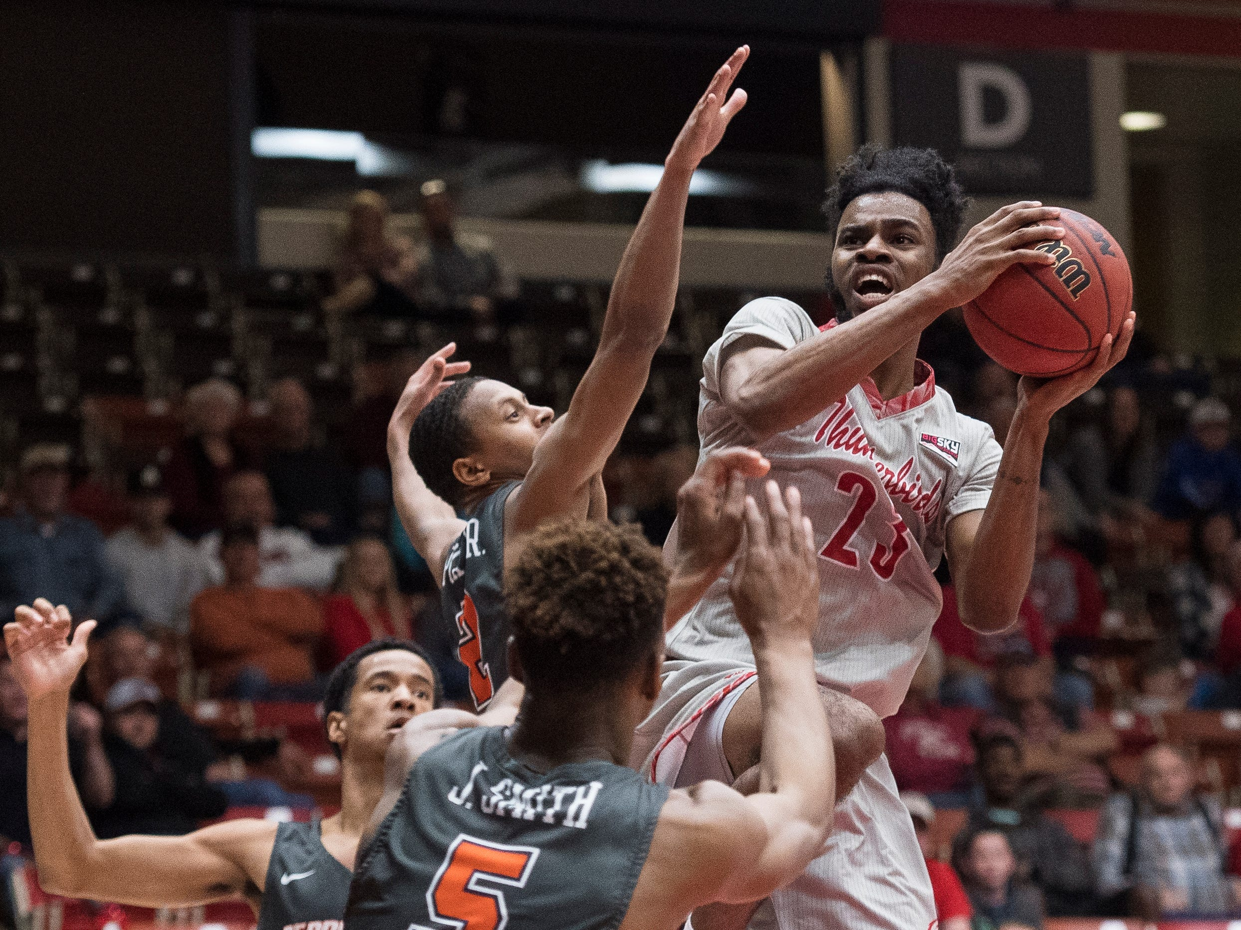 Southern Utah University junior Cameron Oluyitan (23) fights for a basket against Pepperdine University in the America First Event Center Saturday, December 15, 2018. SUU won in overtime, 78-69.