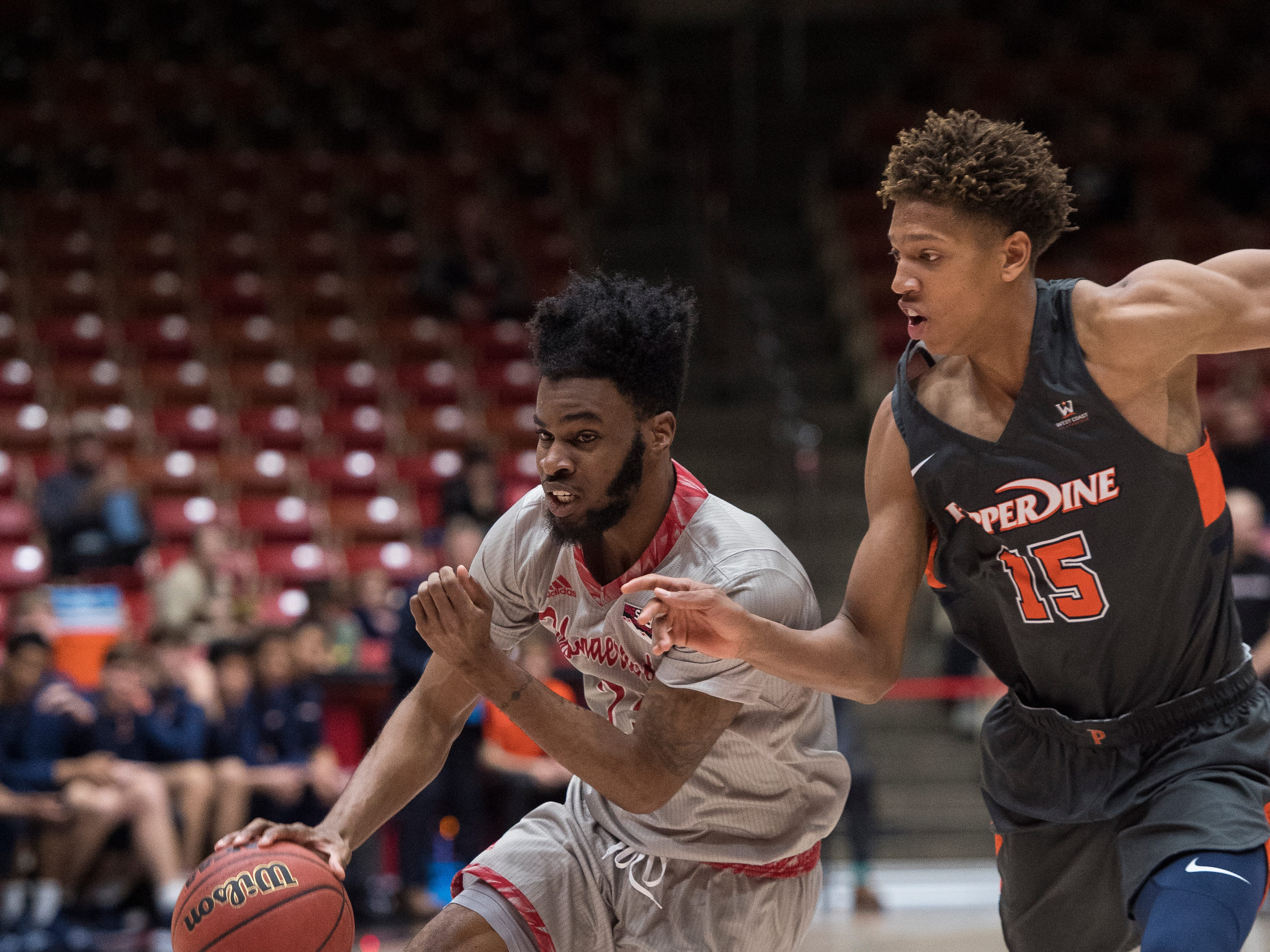 Southern Utah University junior Cameron Oluyitan (23) runs for the basket against Pepperdine University in the America First Event Center Saturday, December 15, 2018. SUU won in overtime, 78-69.