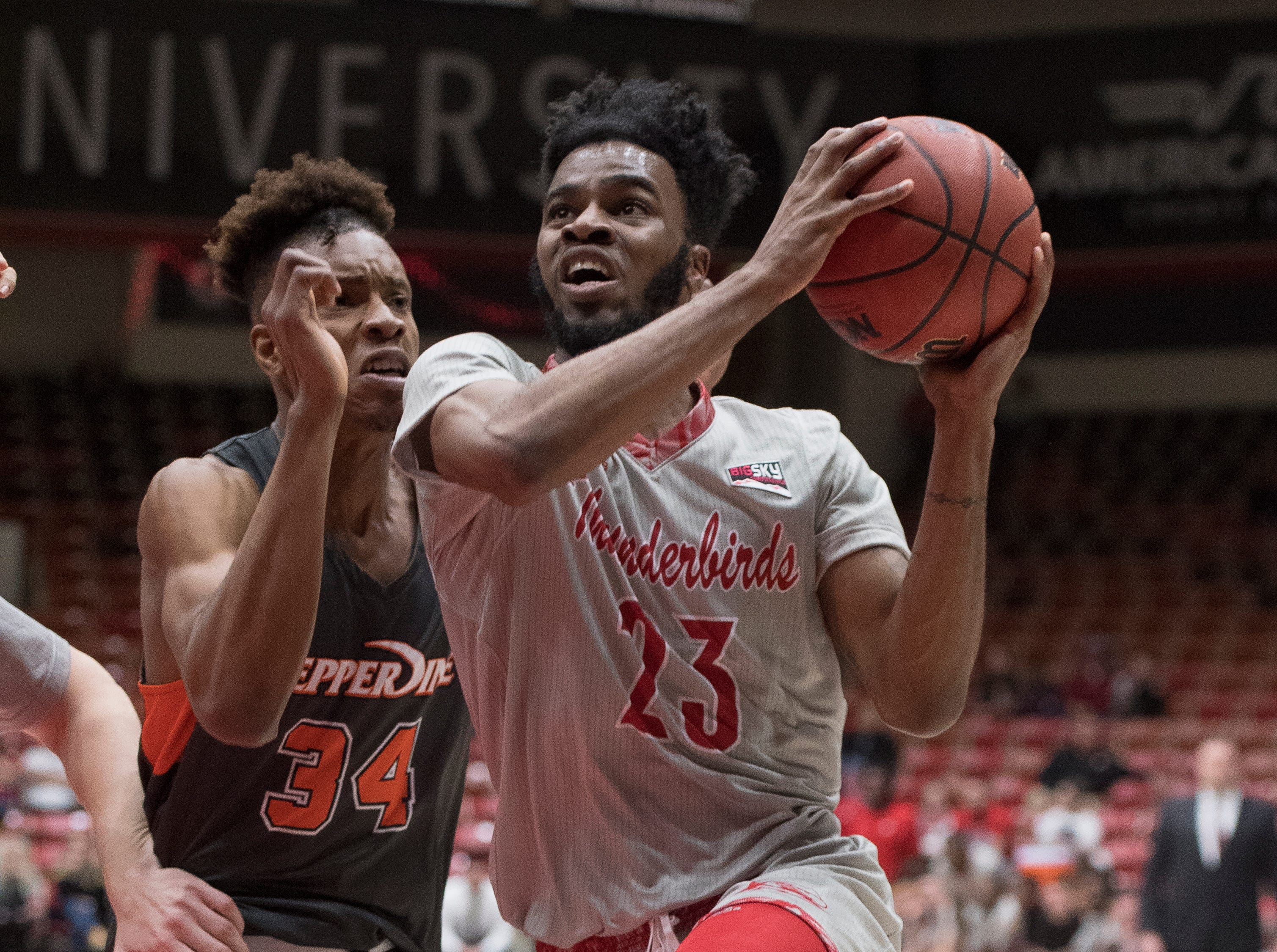 Southern Utah University junior Cameron Oluyitan (23) scores a basket during the game against Pepperdine University in the America First Event Center Saturday, December 15, 2018. SUU won in overtime, 78-69.