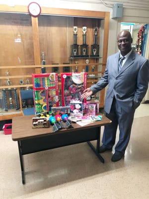 Carter-Parramore Academy principal Dr. Willie Jackson poses items collected in the first batch of FAMU's toy drive.