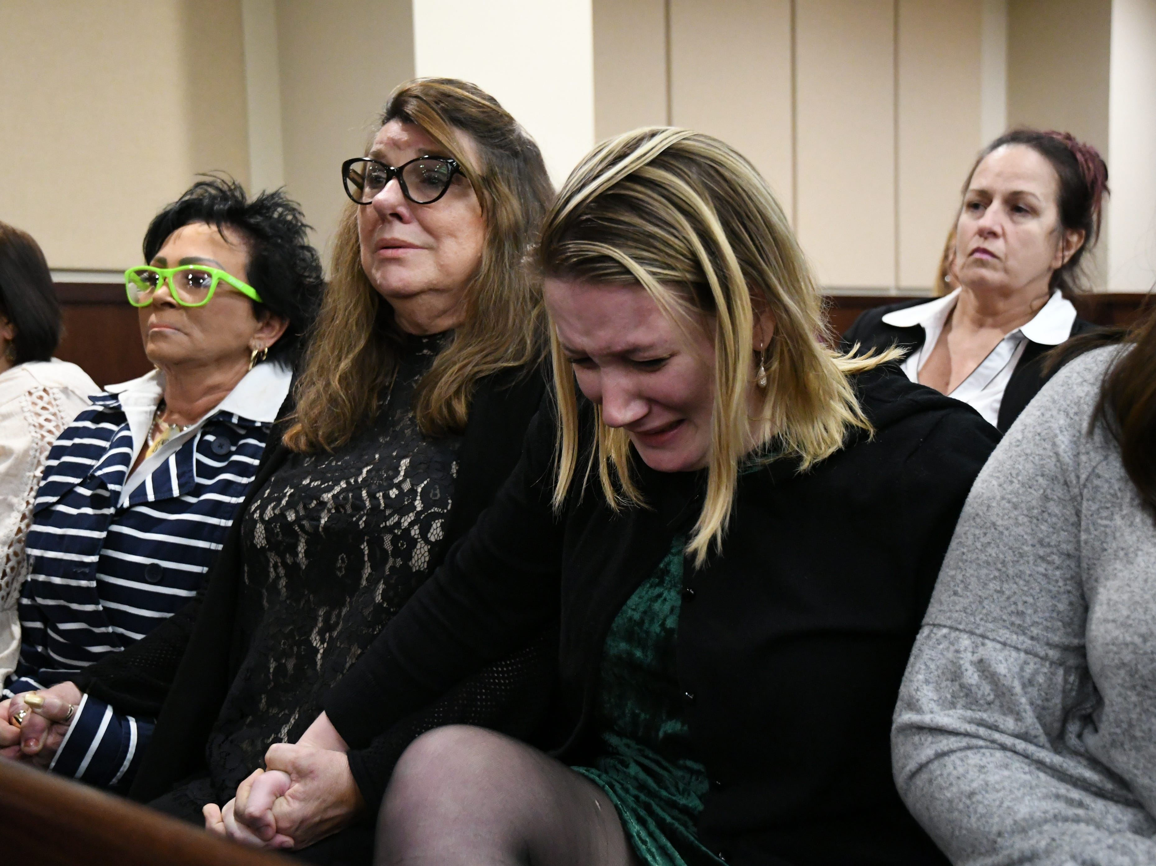 Mary Christy Denmark, center, a close family friend of Mike Williams, the man who was shot and killed by his best friend Brian Winchester, grasps her daughter's hand, Marya Denmark, right, as the verdicts are announced in the trial against Denise Williams for the murder of her husband, Mike Williams, Friday, Dec. 14, 2018.