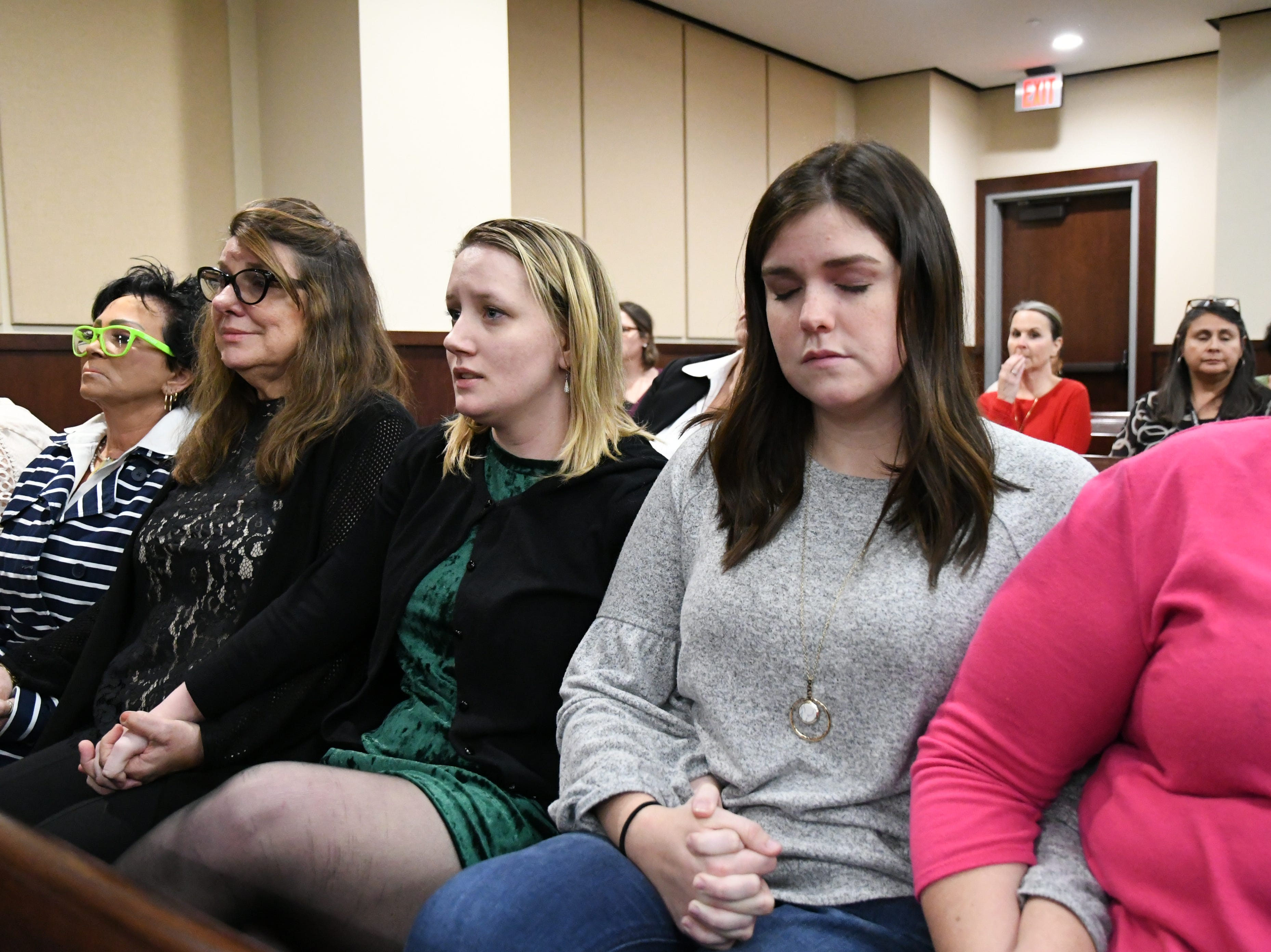 Family and friends of Mike Williams, the man who was shot and killed by Brian Winchester, his high school best friend, hold hands while they await the verdicts in the trial against Denise Williams, the former wife of Mike Williams, Friday, Dec. 14, 2018.