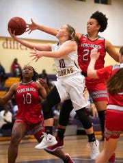 Fort Pierce Central's Maryanne Logsdon (center) puts a shot up against Vero Beach's Cheyenne Marshall in the first half of their game at Fort Pierce Central High School on Friday, Dec. 14, 2018, in Fort Pierce.
