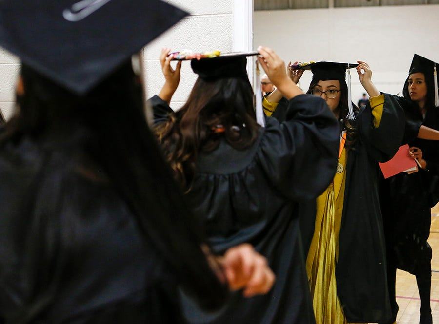 Students adjust their caps before UTEP winter commencement Saturday.