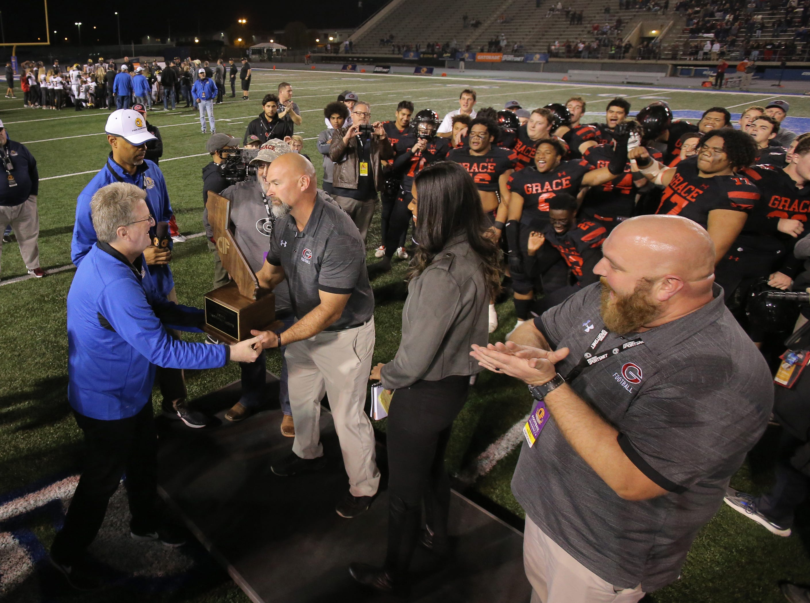 Grace Brethren head coach Josh Henderson receives the state championship trophy after his team defeated Del Oro 21-14 for the Division 2AA title Friday at Cerritos College.