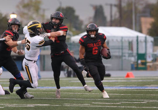 Josh Henderson blocks Del Oro's Blake Demar to give Lontrelle Diggs a bigger opening to run through during the Grace Brethren's 21-14 victory in the Division 2AA state championship game Friday at Cerritos College.