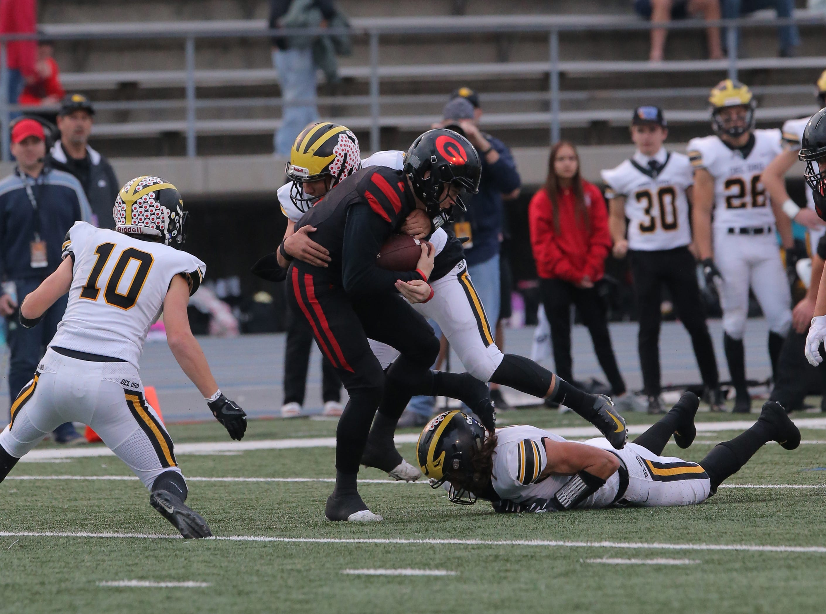 Grace Brethren quarterback Mikey Zele is surrounded by Del Oro defenders during the Division 2AA state championship game Friday at Cerritos College. The Lancers won, 21-14.