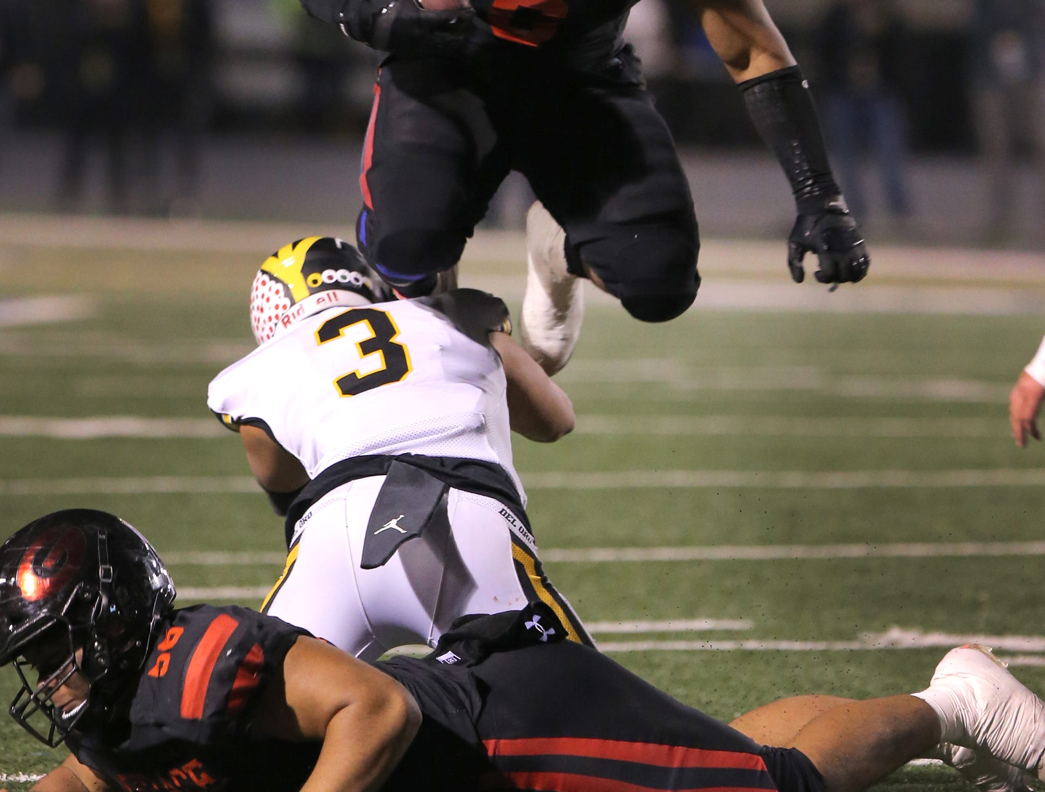 Grace Brethren's Lontrelle Diggs hurdles over Del Oro's Dante Pericin during the Lancers' 21-14 victory in the Division 2AA state championship game Friday at Cerritos College.