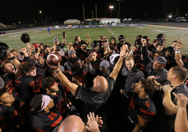 Head coach Josh Henderson and Grace Brethren celebrate after the Lancers beat Del Oro 21-14 in the Division 2AA state championship game Friday at Cerritos College.