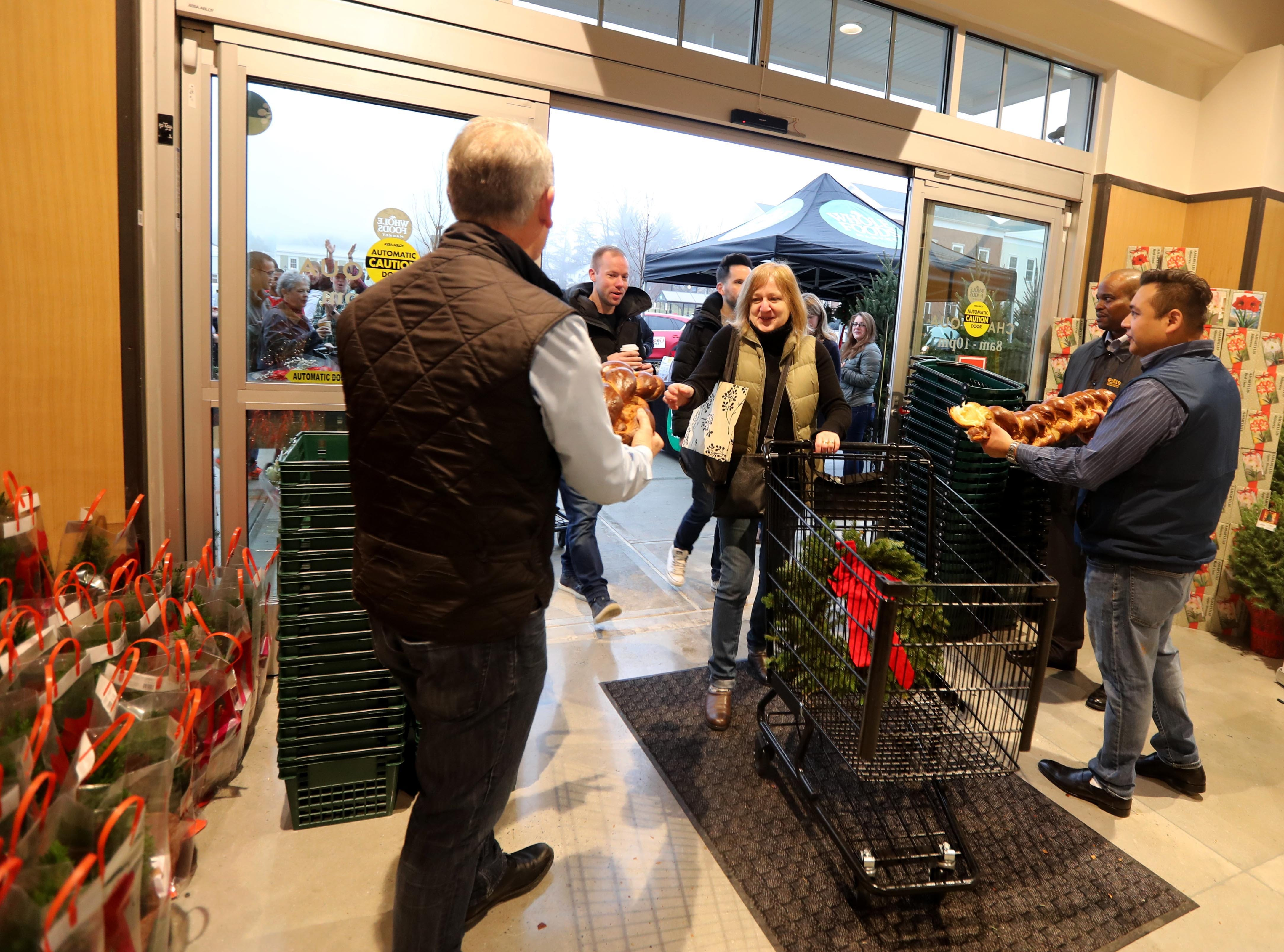 Whole Foods employees hand pieces of bread to the first shoppers during the grand opening of the supermarket at Chappaqua Crossing  Dec. 15, 2018. The 40,000 square foot store opened to shoppers on the site of the formers Readers Digest headquarters. The New Castle Town Board and Planning Board approved a temporary traffic plan for the Route 117-Roaring Brook Road intersection that allowed the store to open.