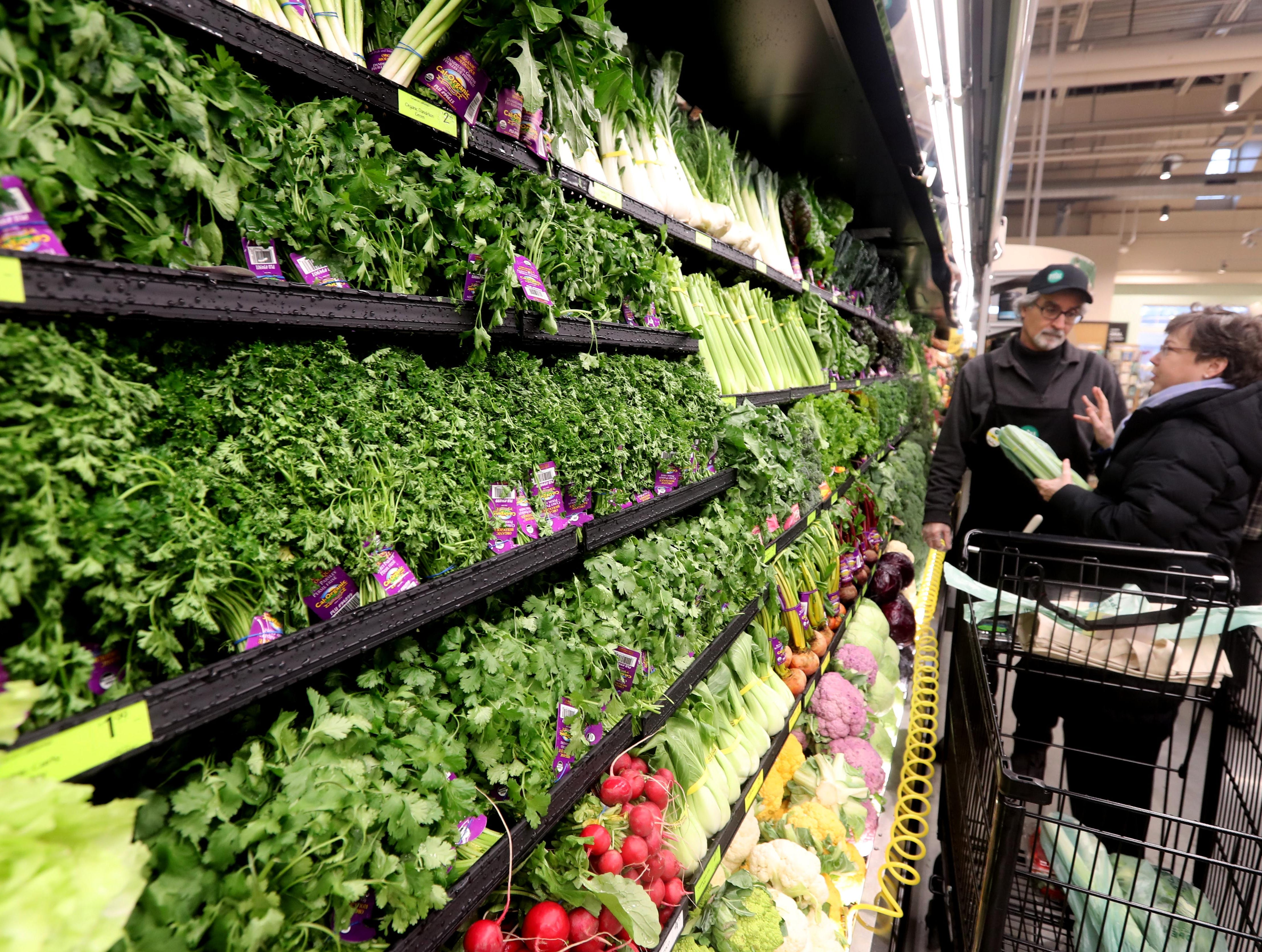 Whole Foods employee John Pollara assists Genny Holland of Pleasantville select produce in new Whole Foods in Chappaqua shortly after the grand opening of the supermarket at Chappaqua Crossing  Dec. 15, 2018. The 40,000 square foot store opened to shoppers on the site of the formers Readers Digest headquarters. The New Castle Town Board and Planning Board approved a temporary traffic plan for the Route 117-Roaring Brook Road intersection that allowed the store to open.