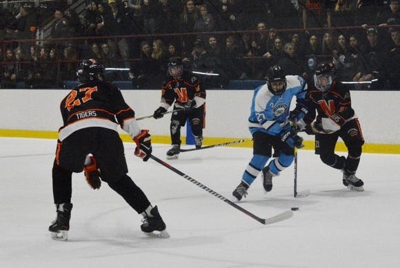 Suffern forward Ryan Fennell attempts to split the Mamaroneck defenders in the first period of a 2-0 win over the Tigers.  He scored the second goal of the game.