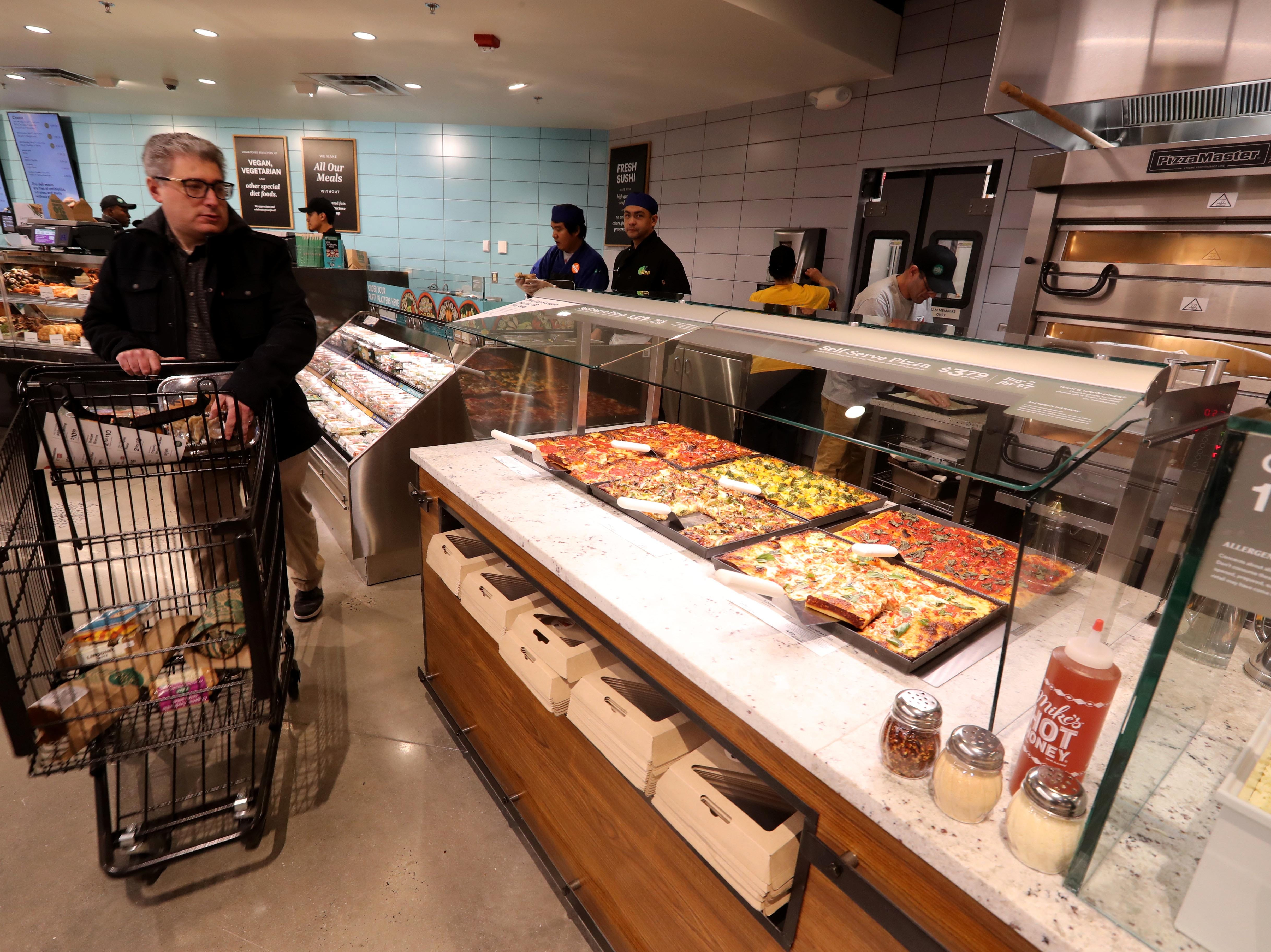 A shopper peruses the self-service pizza buffet at the new Whole Foods in Chappaqua Dec. 15, 2018. The 40,000 square foot store opened to shoppers on the site of the formers Readers Digest headquarters. The New Castle Town Board and Planning Board approved a temporary traffic plan for the Route 117-Roaring Brook Road intersection that allowed the store to open.