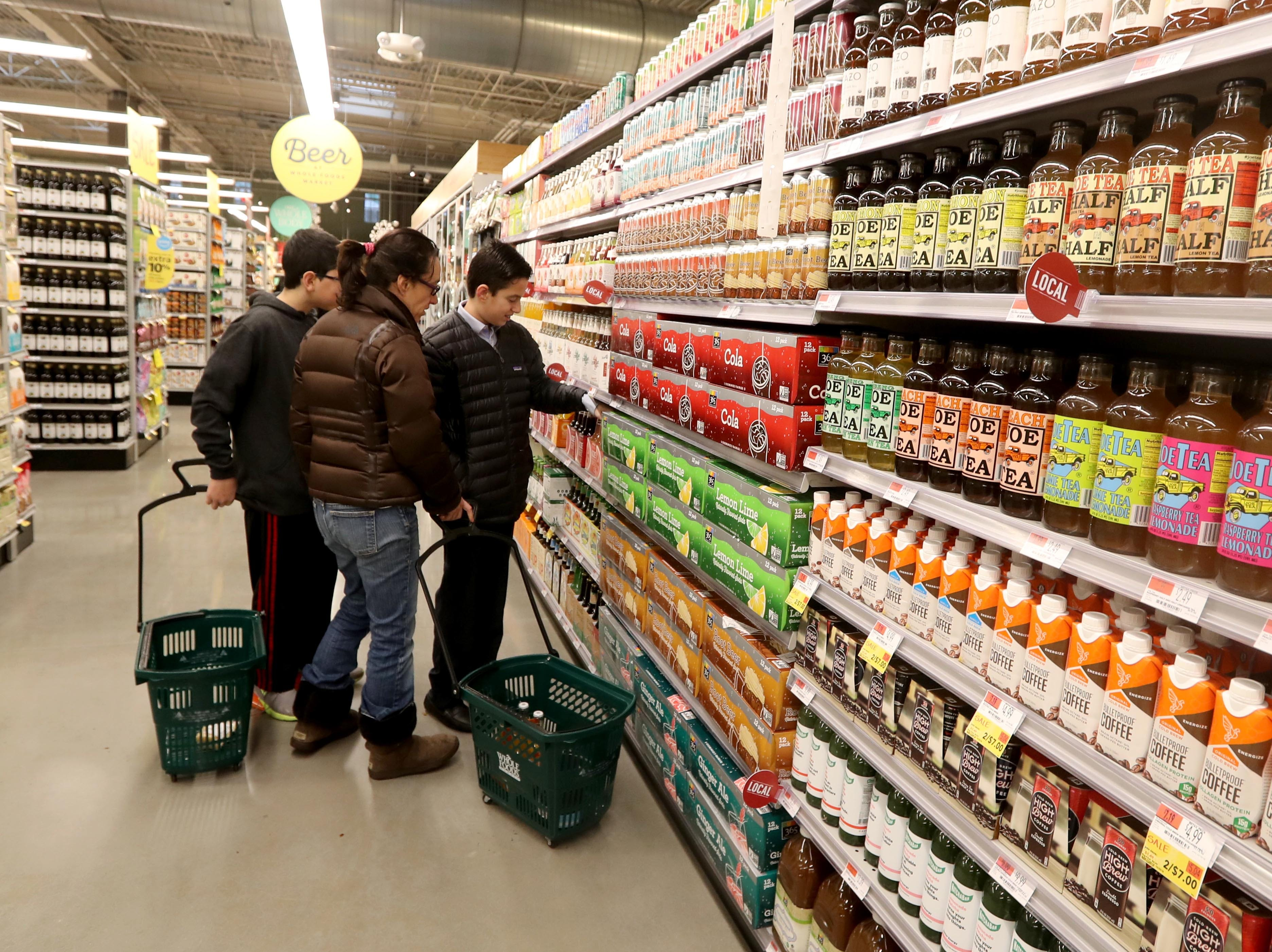 Stacy Gross, her son, Max, 13, and Aaron Silver, 13, shop for beverages in new Whole Foods in Chappaqua shortly after the grand opening of the supermarket at Chappaqua Crossing  Dec. 15, 2018. The 40,000 square foot store opened to shoppers on the site of the formers Readers Digest headquarters. The New Castle Town Board and Planning Board approved a temporary traffic plan for the Route 117-Roaring Brook Road intersection that allowed the store to open.