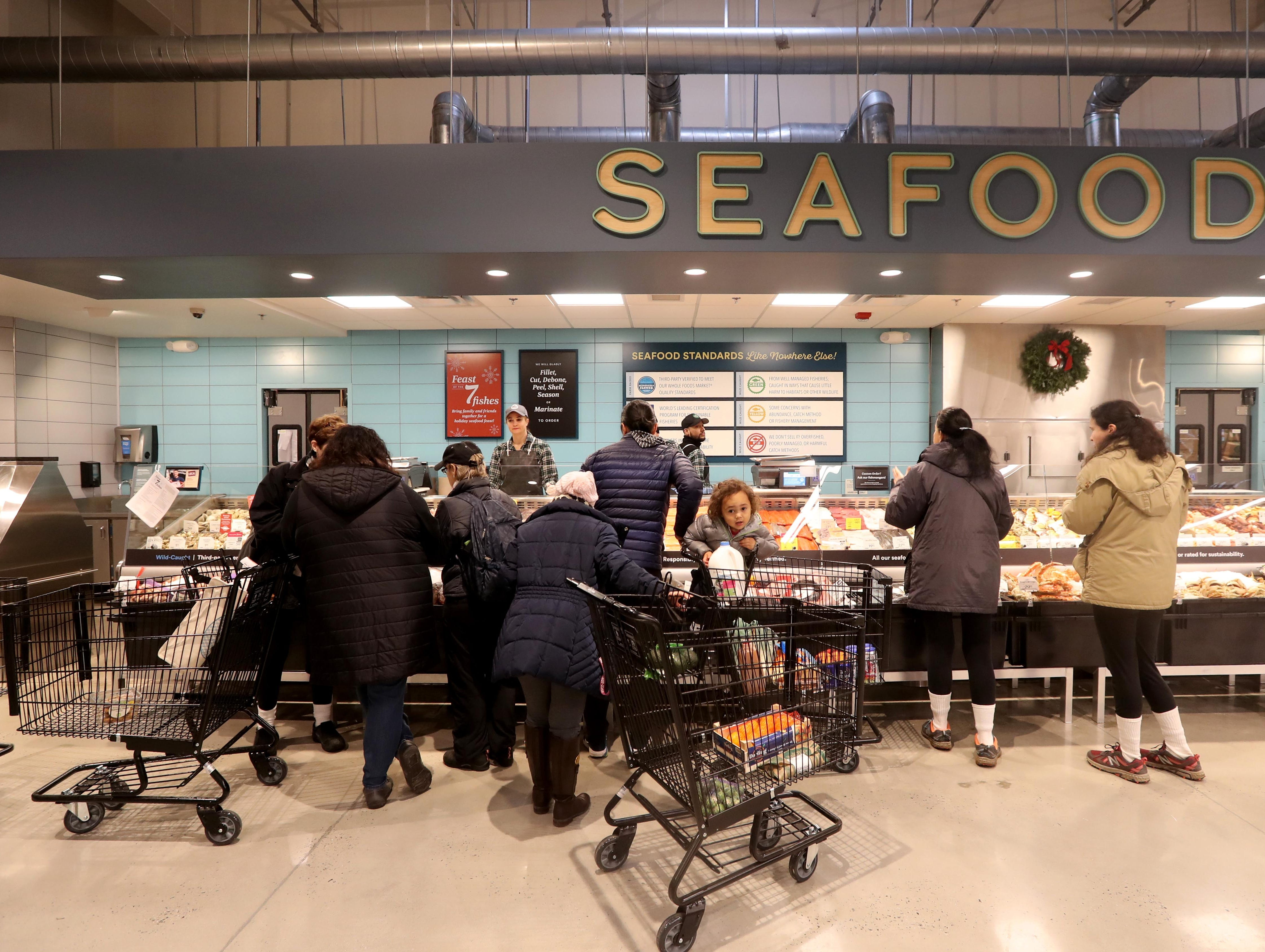 Shoppers stop by the seafood section at the new Whole Foods in Chappaqua Dec. 15, 2018. The 40,000 square foot store opened to shoppers on the site of the formers Readers Digest headquarters. The New Castle Town Board and Planning Board approved a temporary traffic plan for the Route 117-Roaring Brook Road intersection that allowed the store to open.