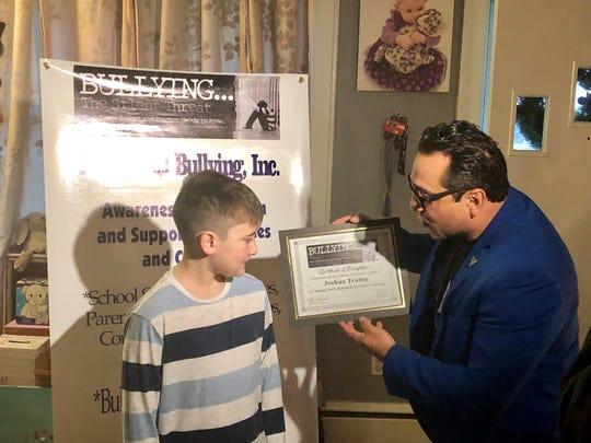 Claudio Cerullo, founder of the non-profit Teach Anti Bullying, presents Talley Middle School student Joshua Trump with an award recognizing his courage in going through schoolyard teasing and bullying over his last name.