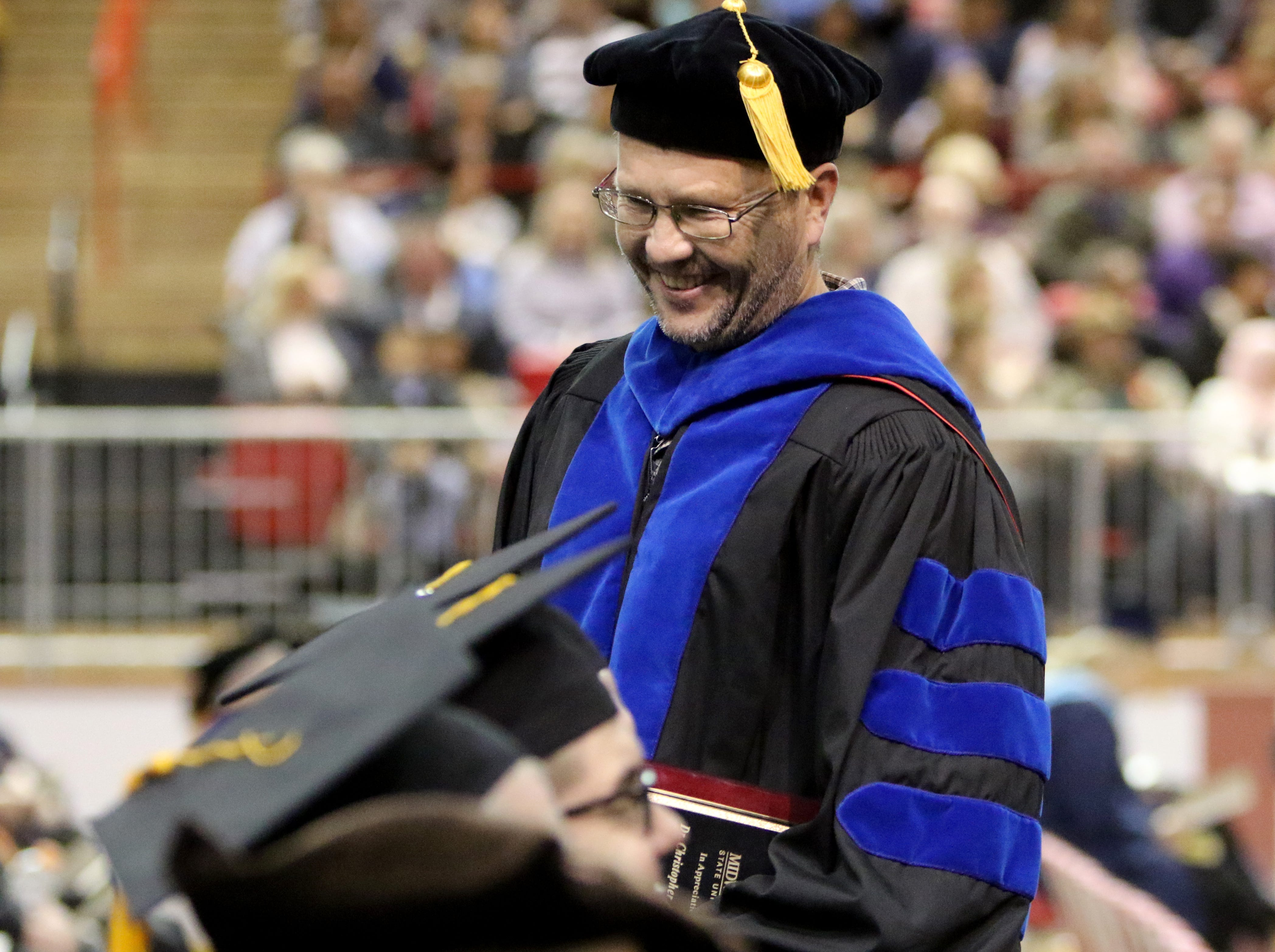 Midwestern State University Associate Professor of chemistry Chris Hansen returns to his seat after recieving his Faculty Award at the fall commencement ceremony Saturday, Dec. 15, 2018, in Kay Yeager Coliseum at the MPEC. The award is given to ful-time faculty members for teaching excellance and service to the university.