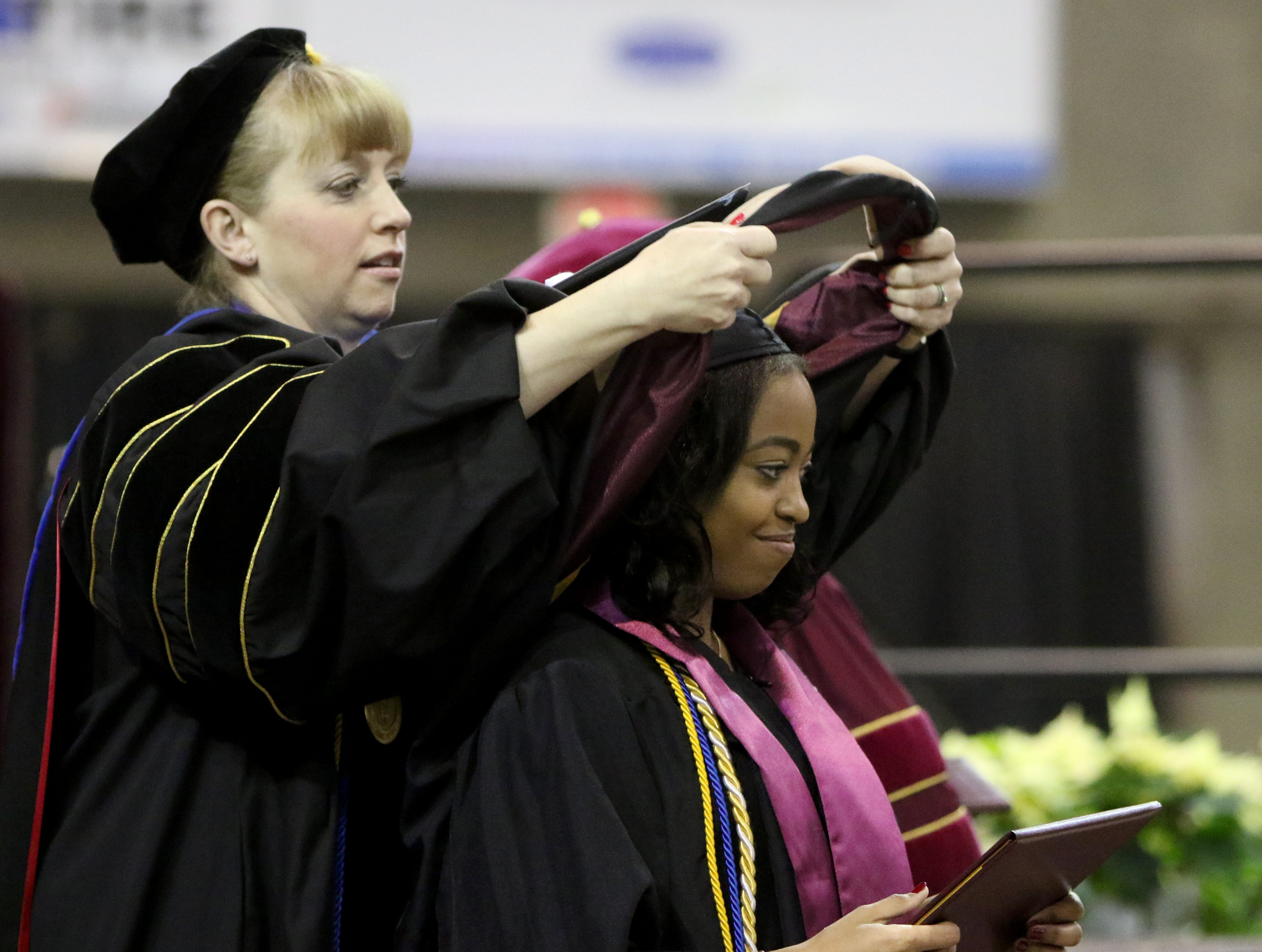 Midwestern State University masters graduate Rolanda Ferdinand is hooded at the fall commencement ceremony Saturday, Dec. 15, 2018, in Kay Yeager Coliseum at the MPEC.