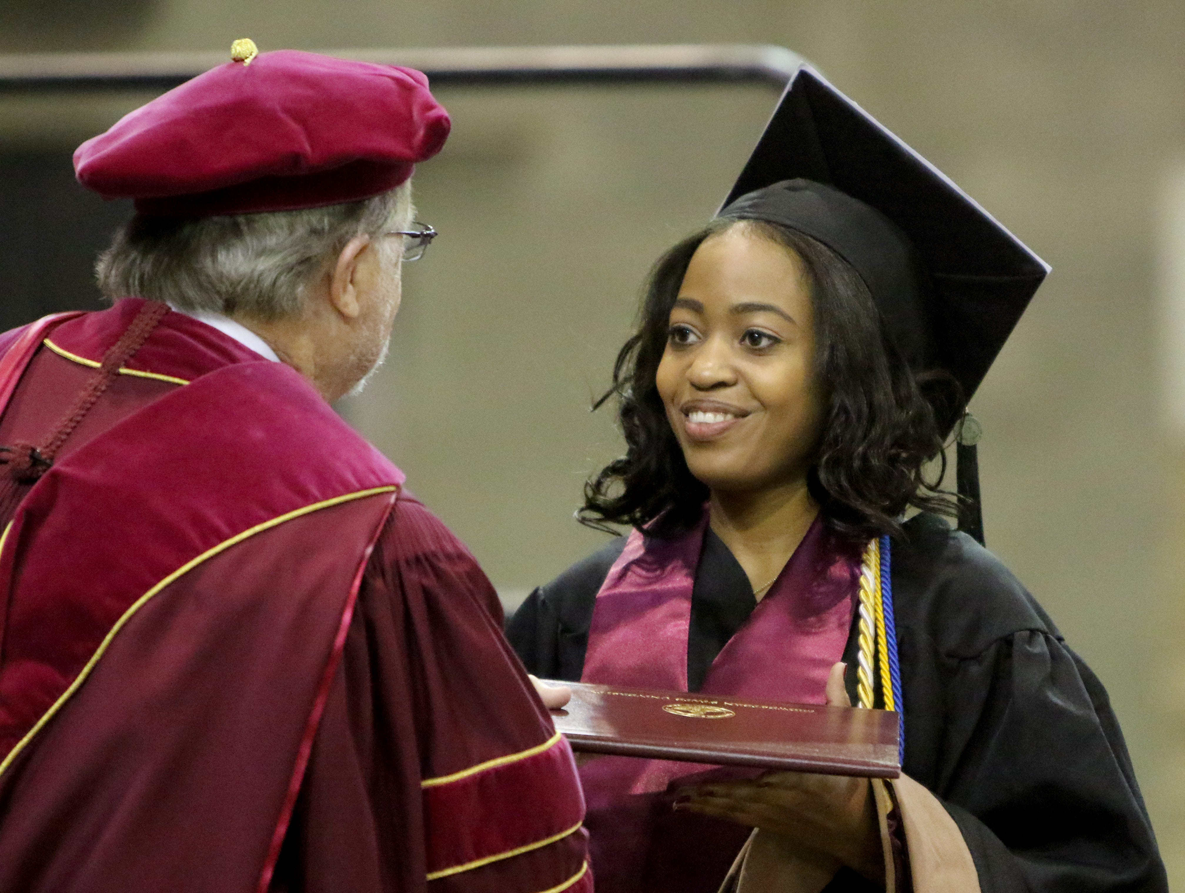 Midwestern State University masters graduate Rolanda Ferdinand receives her degree folder at the fall commencement ceremony Saturday, Dec. 15, 2018, in Kay Yeager Coliseum at the MPEC.