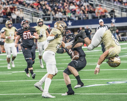 Aledo junior quarterback Jake Bishop tries to slide between Rider's Dominique Horton (24) and Bodie Oliver (33) during a Class 5A Division II semifinal game at AT&T Stadium in Arlington.