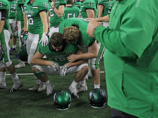 Iowa Park's Wyatt Edwards is consoled by a teammate after the Hawks 49-14 loss to Pleasant Grove in the Class 4A Division II semifinal Friday, Dec. 14, 2018, at the Ford Center in Frisco.