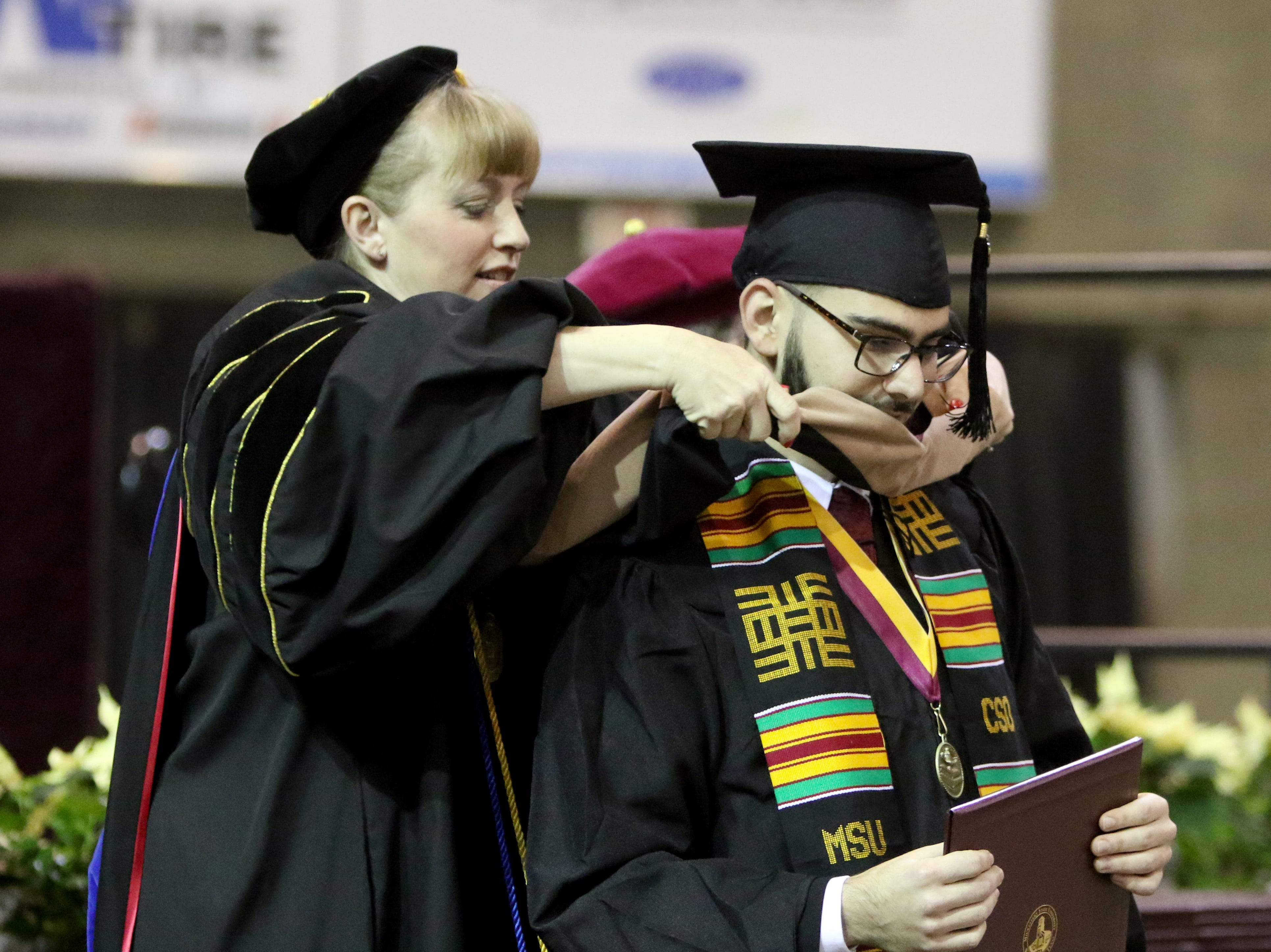 Midwestern State University masters graduate Habib Hadeed is hooded at the MSU fall commencement ceremony Saturday, Dec. 15, 2018, in Kay Yeager Coliseum at the MPEC.