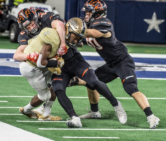 Rider sophomore Nick Darcus (2) is wrapped up by Aledo's Ryan Anderson with Tatum Price in pursuit during a Class 5A Division II semifinal game at AT&T Stadium in Arlington.