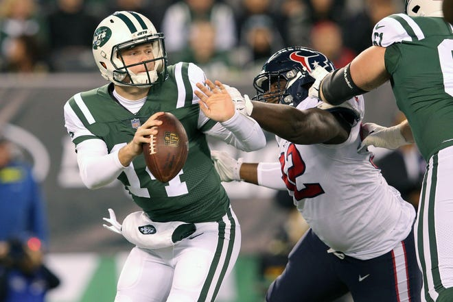 New York Jets quarterback Sam Darnold (14) breaks free of pressure by Houston Texans nose tackle Brandon Dunn (92) during the first quarter at MetLife Stadium.