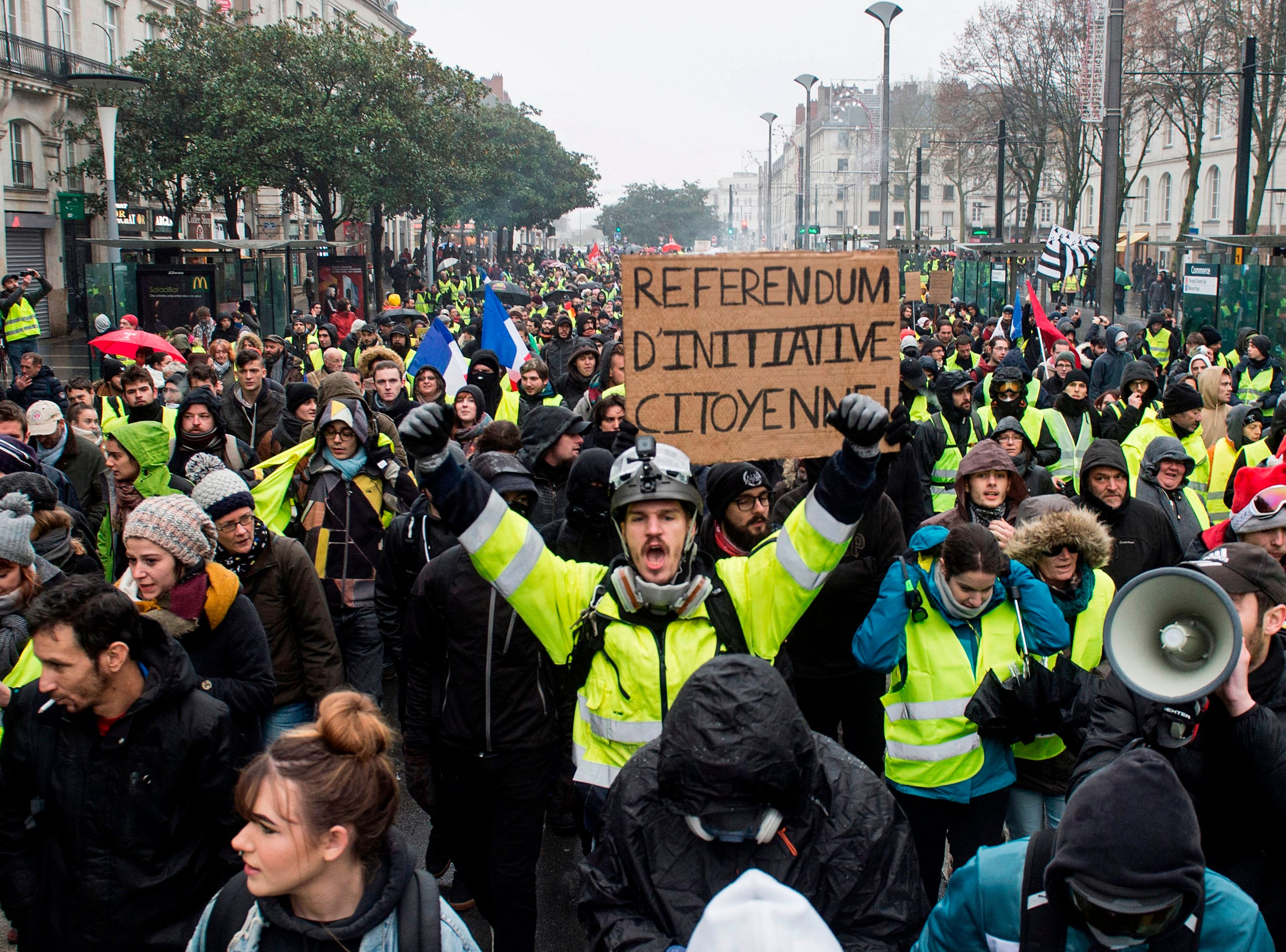 "A protester wearing a yellow vest (gilet jaune) holds a placard reading ""citizens' referendum initiative"" as they protest against rising costs of living they blame on high taxes in Nantes, on Dec. 15, 2018."