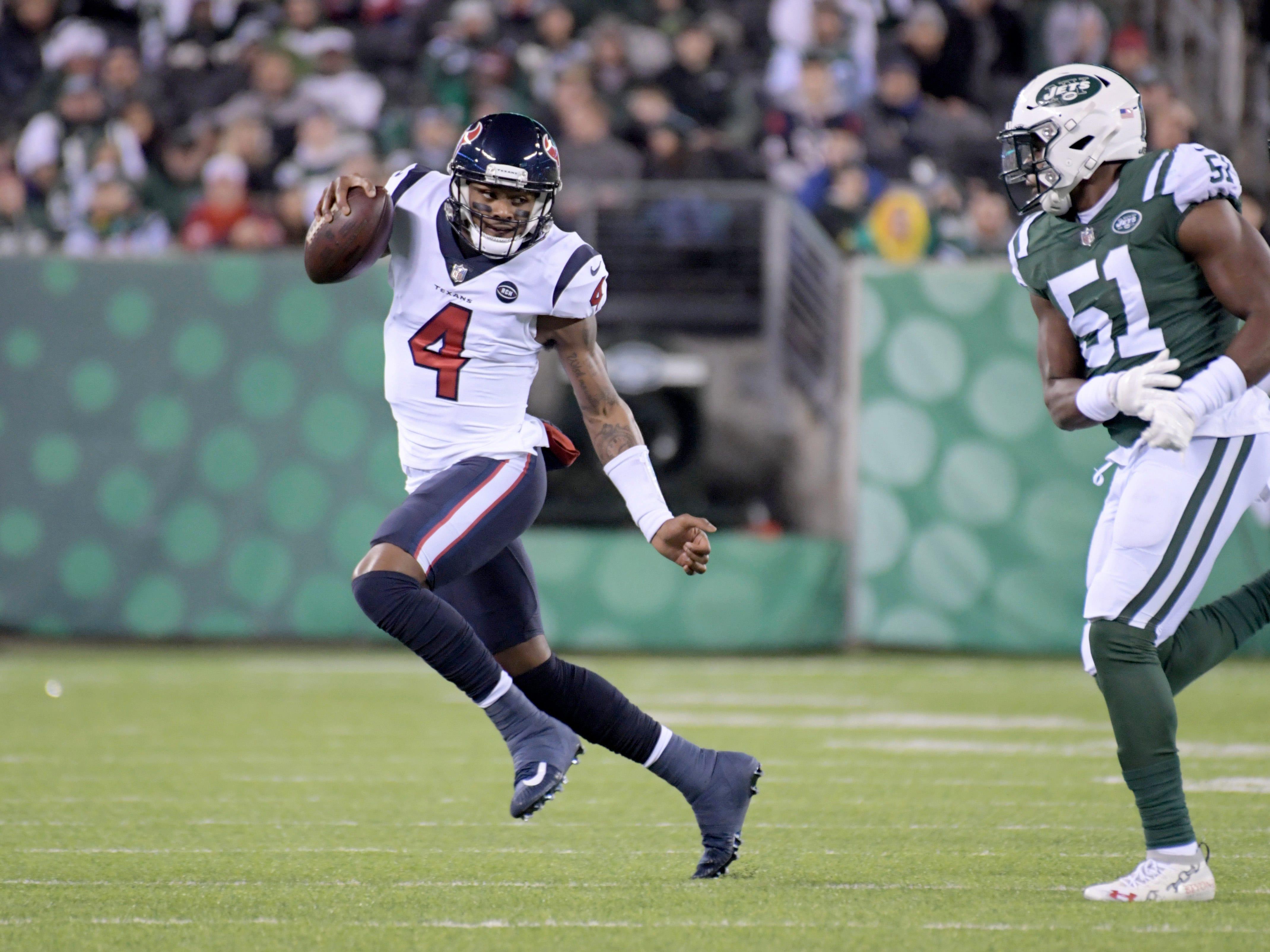 Houston Texans quarterback Deshaun Watson (4) runs from New York Jets outside linebacker Brandon Copeland (51) during the first half at MetLife Stadium.
