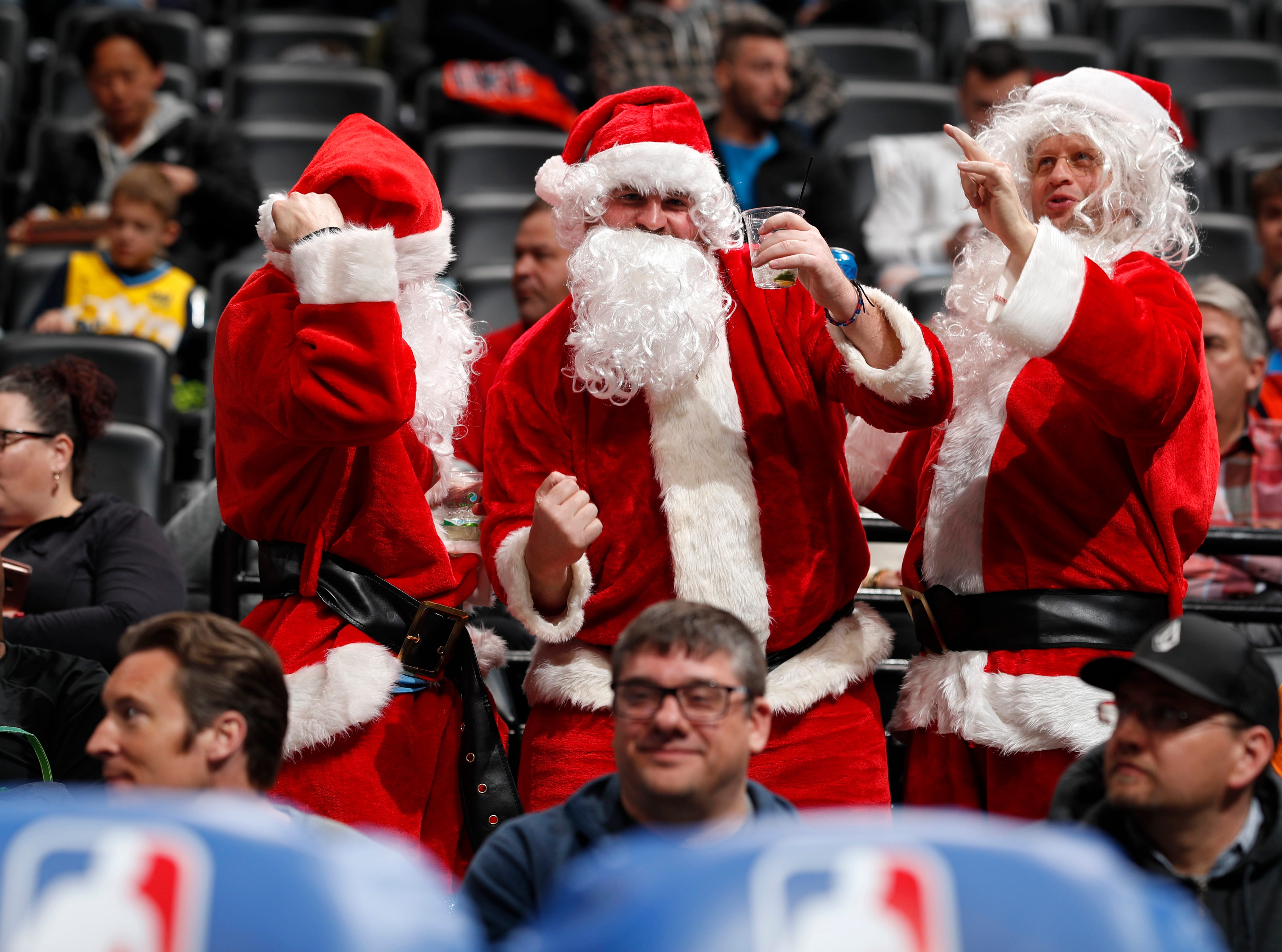 Fans dressed as Santa Claus dance behind the Oklahoma City Thunder bench in the first half of an NBA basketball game against the Denver Nuggets Friday, Dec. 14, 2018, in Denver.