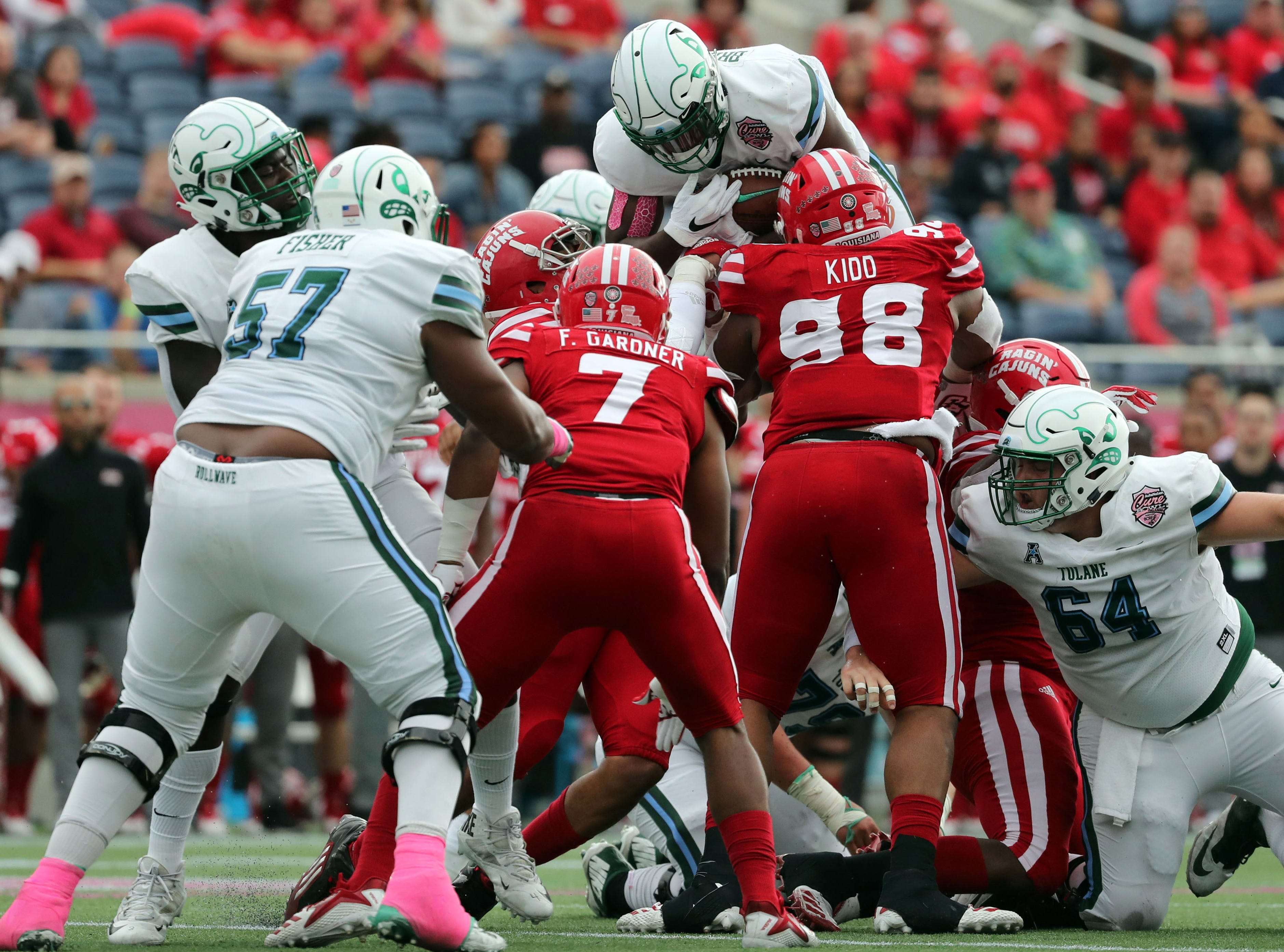 Tulane Green Wave running back Darius Bradwell (10) jumps over Louisiana-Lafayette Ragin' Cajuns defensive tackle LaDarrius Kidd (98) in the Cure Bowl.
