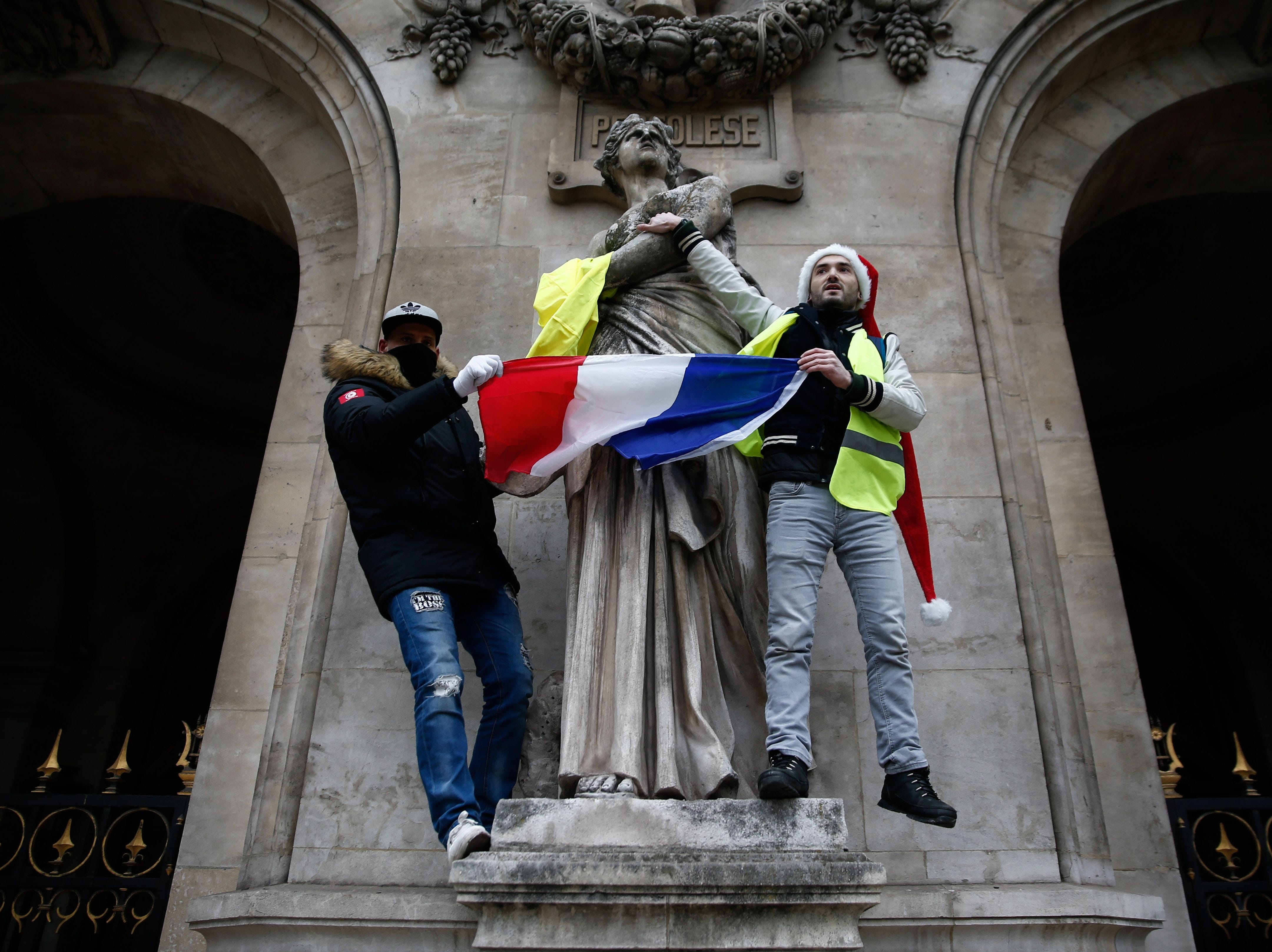 Protesters wearing a yellow vest (gilets jaunes) wave the French national flag during a demonstration against rising costs of living blamed on high taxes in Paris, on Dec. 15, 2018.