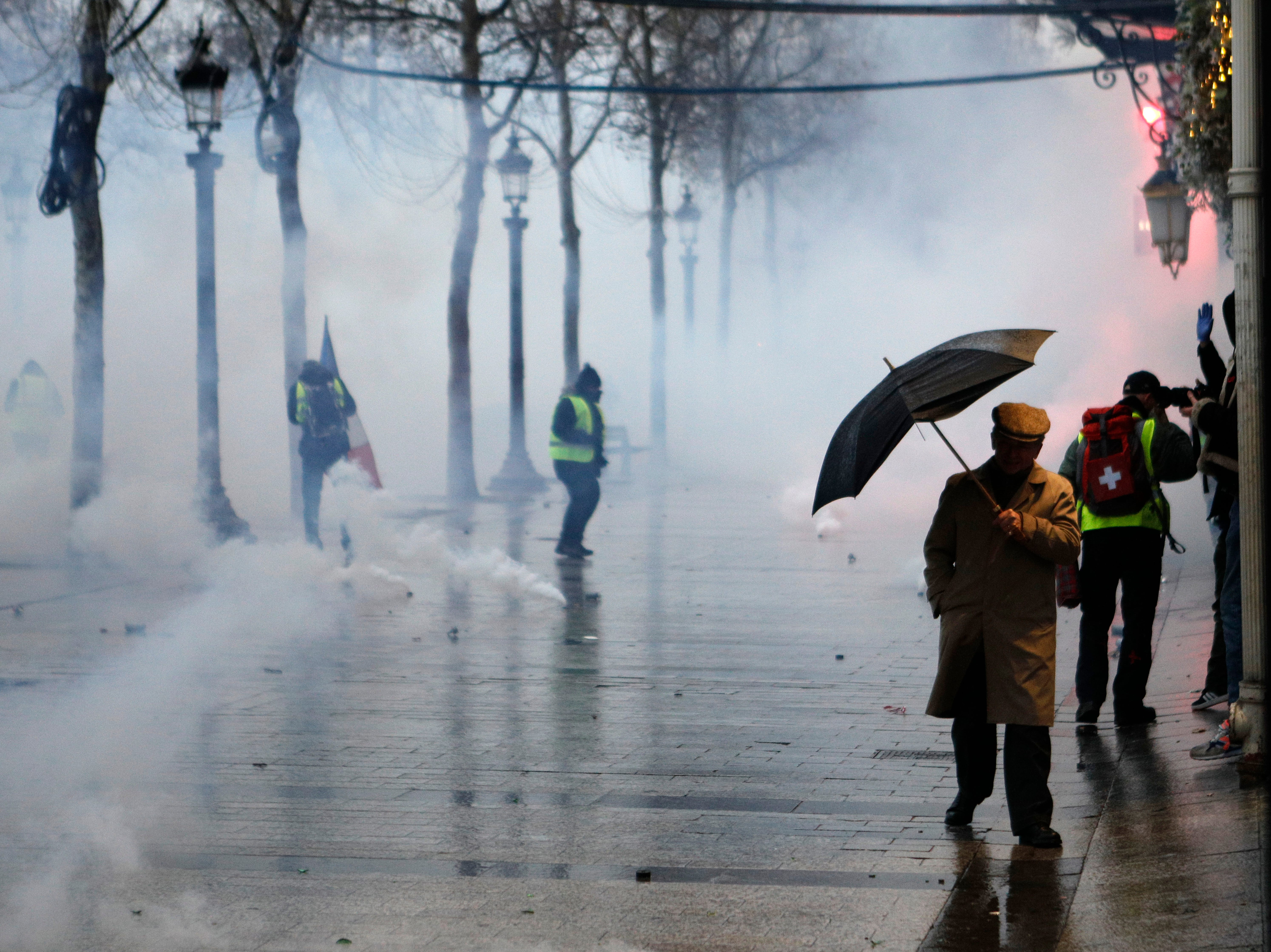 "A man makes his way through tear gas as demonstrators protest on the Champs-Elysees avenue, Saturday, Dec. 15, 2018 in Paris. Paris police say 85 people have been detained in Paris on the fifth straight weekend of protests by the ""yellow vests"" movement, where thousands of people converged in the French capital."