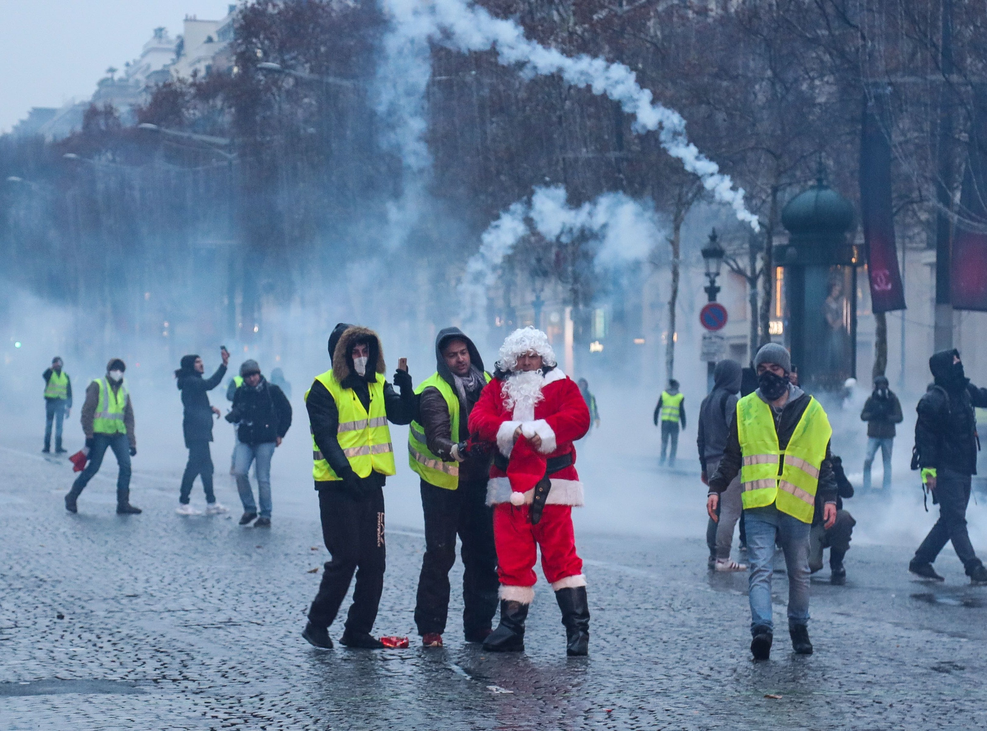 A protester dressed as Santa and wearing a yellow vest (gilet jaune) take part in a demonstration against rising costs of living blamed on high taxes on the Champs-Elysees in Paris, on Dec. 15, 2018.