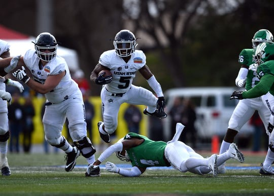 Utah State Aggies running back Darwin Thompson (5) jumps over North Texas Mean Green safety Khairi Muhammad in the New Mexico Bowl.