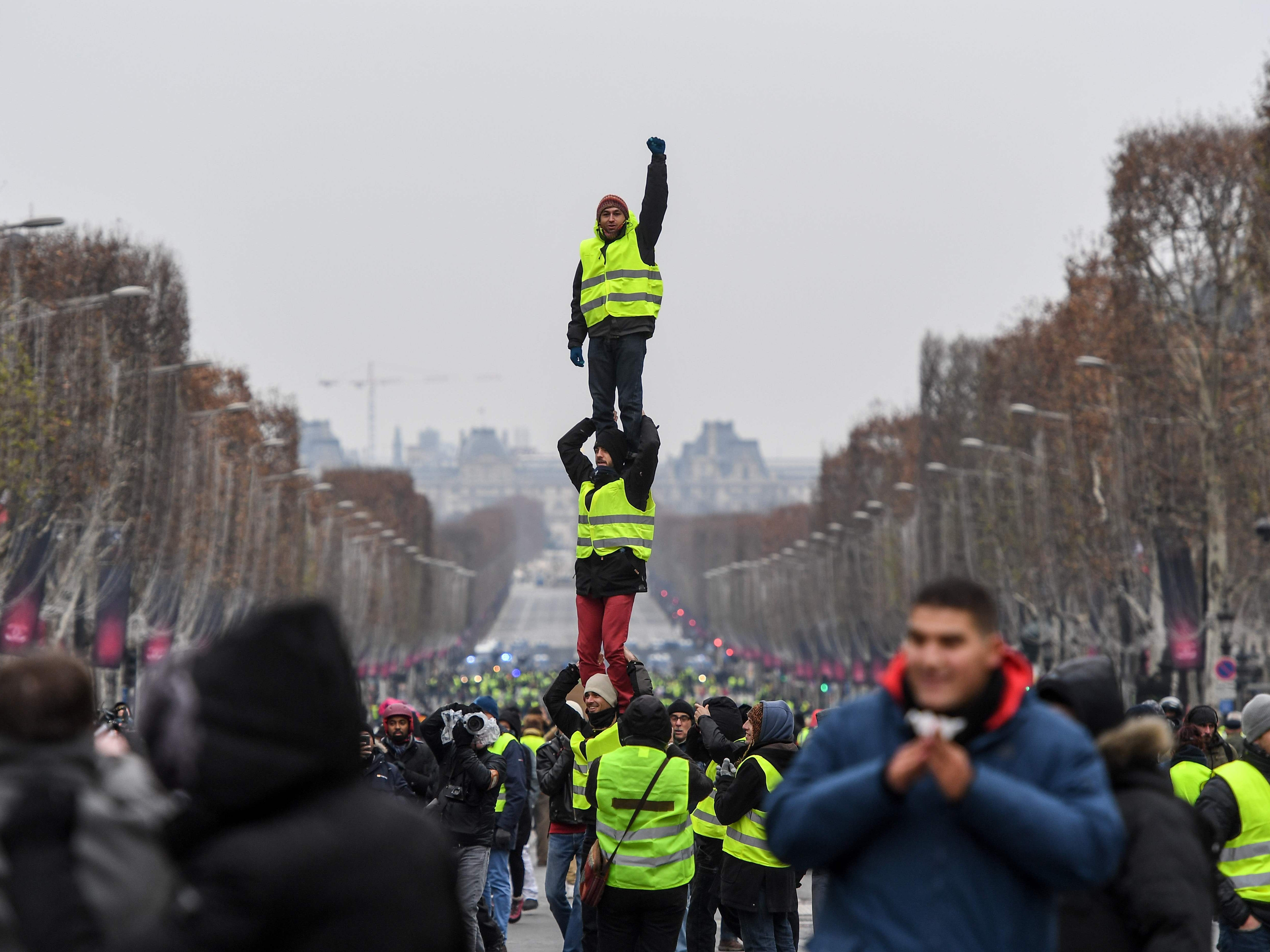 Protesters wearing yellow vests (gilets jaunes) do a human pyramide as they demonstrate against rising costs of living they blame on high taxes in Paris, on Dec. 15, 2018.
