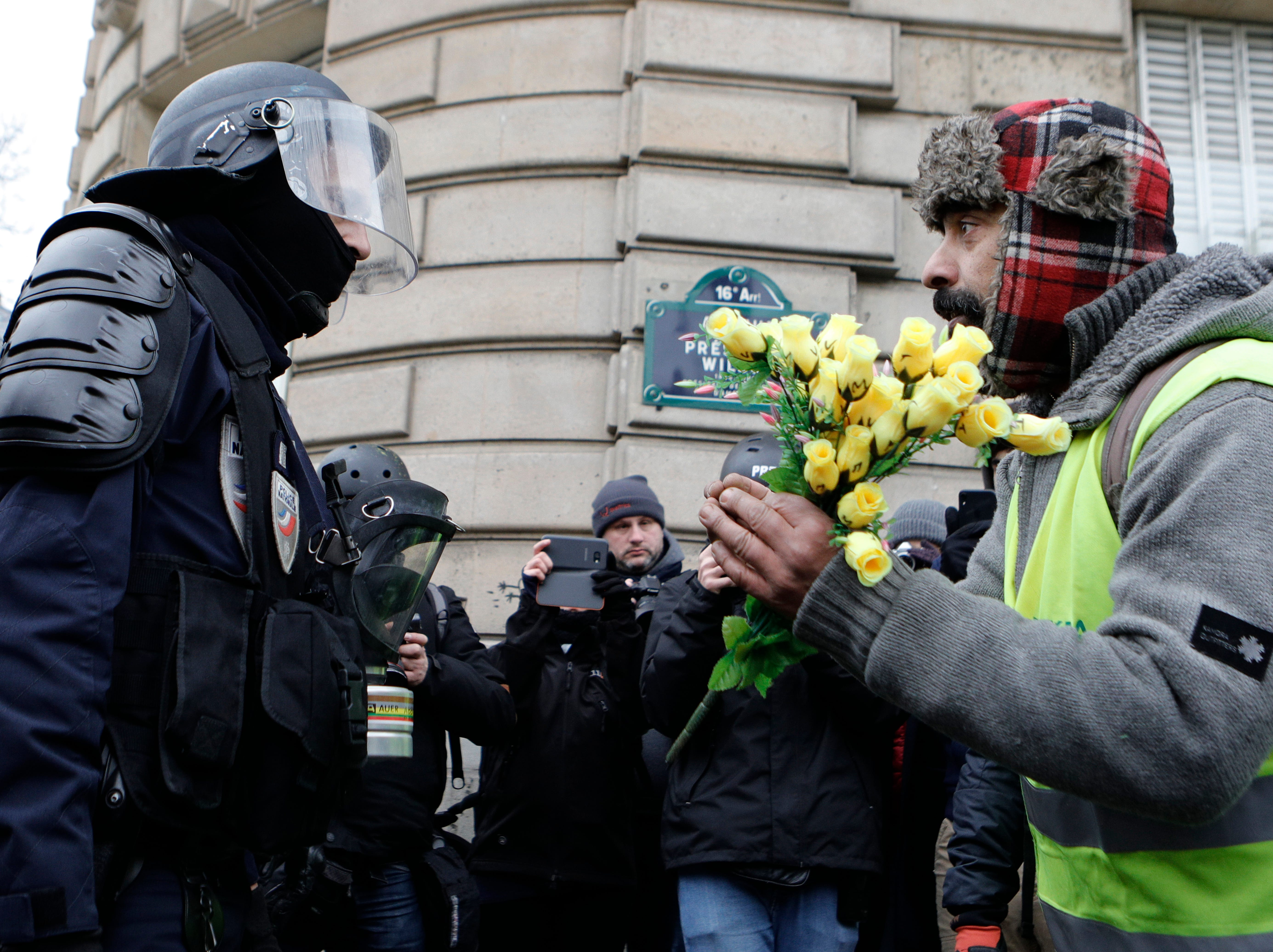 "A demonstrator wearing his yellow vest holds a bouquet of roses in front of a riot police officer during a protest Saturday, Dec. 15, 2018 in Paris. Paris police deployed in large numbers Saturday for the fifth straight weekend of demonstrations by the ""yellow vest"" protesters, with authorities repeating calls for calm after protests on previous weekends turned violent."