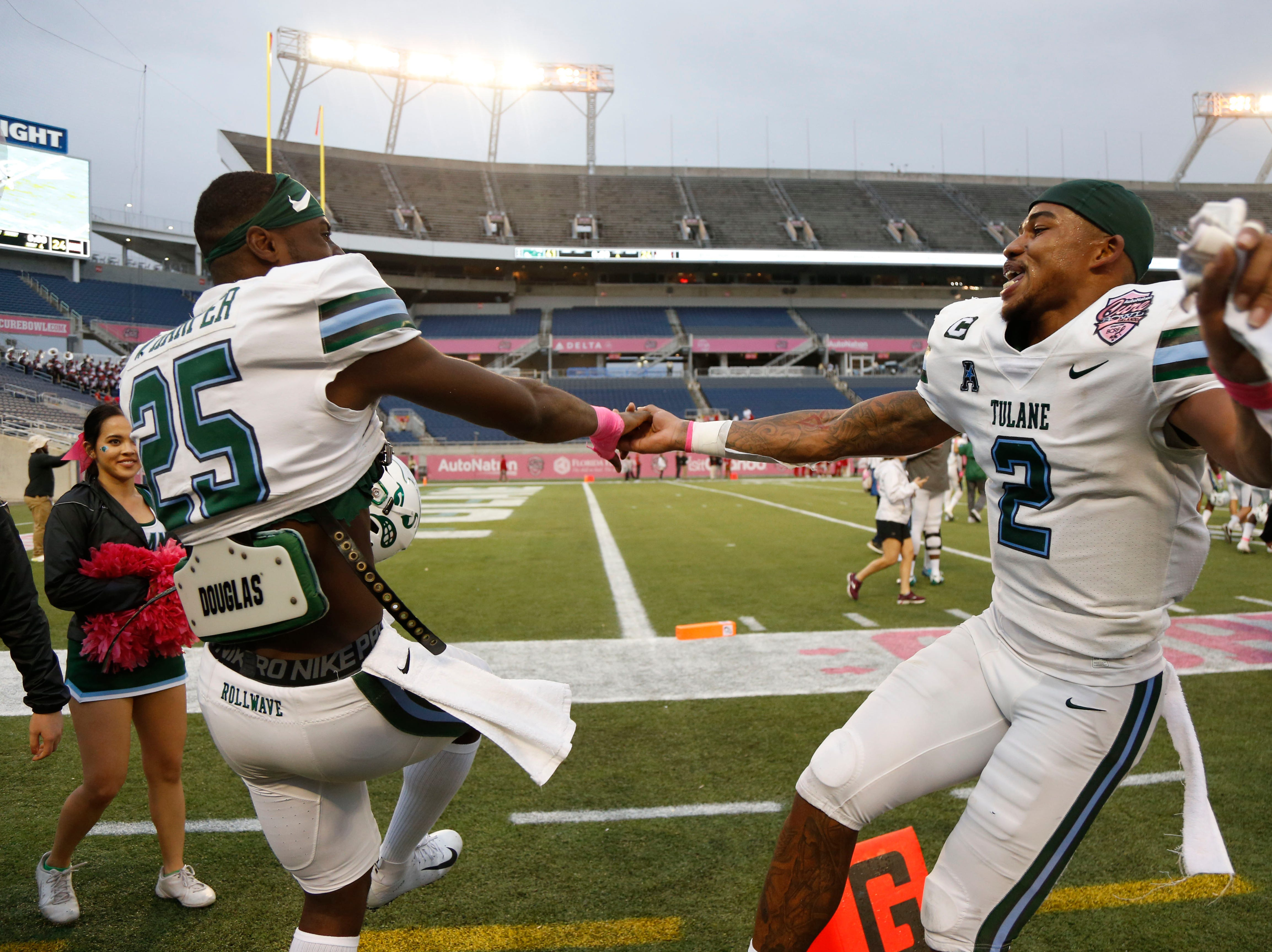 Tulane Green Wave safety Roderic Teamer Jr. (2) and safety Will Harper (25) celebrate as they beat the Louisiana-Lafayette Ragin' Cajuns in the Cure Bowl.