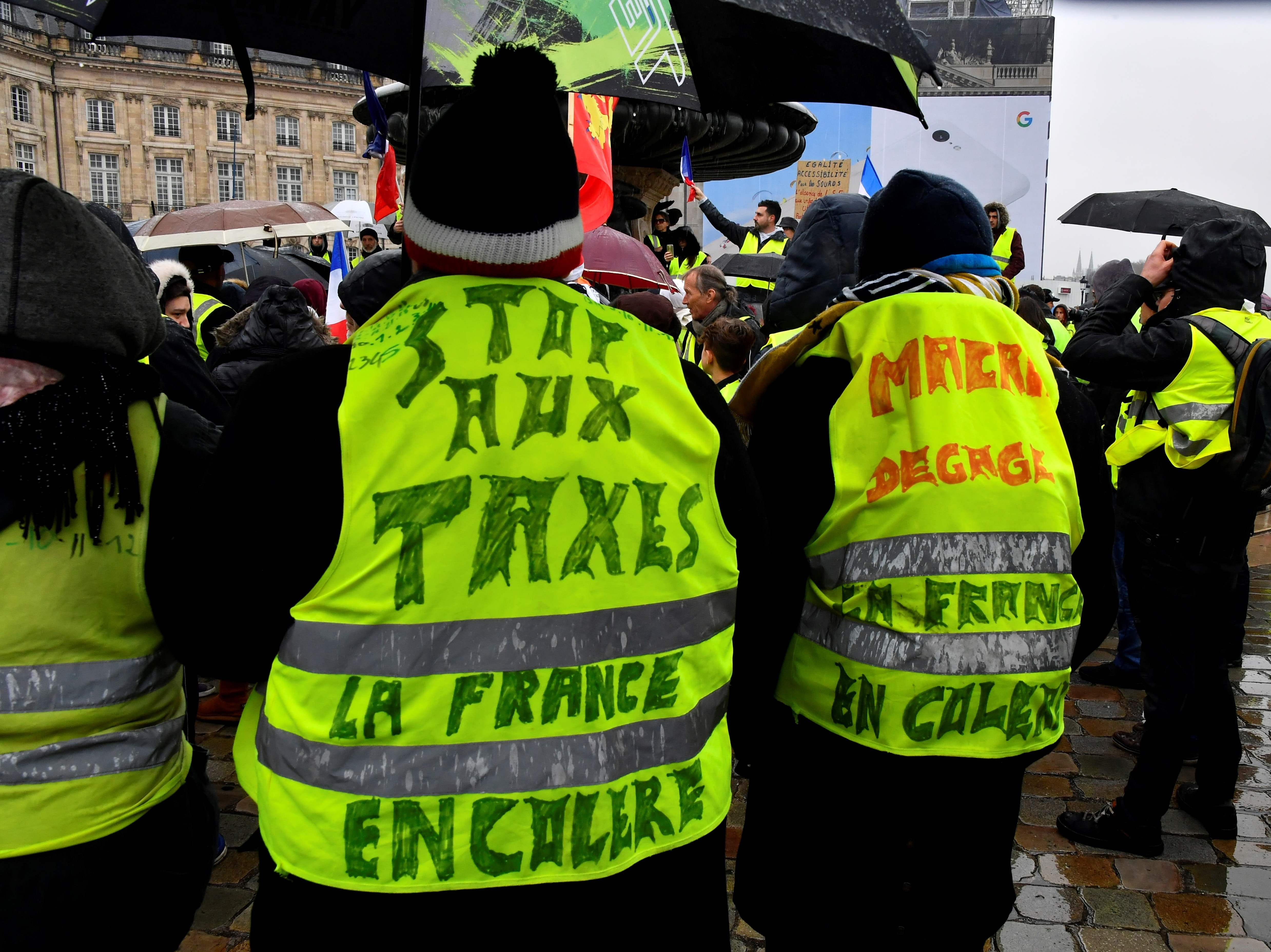 "Protesters wearing yellow vests (gilets jaunes) reading ""Top taxes, France is angry"" demonstrate, on Dec. 15, 2018 in the streets of Bordeaux, south-western France, against rising costs of living they blame on high taxes."