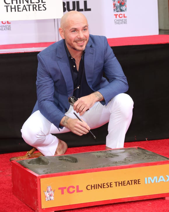 Let the haters hate! Pitbull had his hands and feet immmortalized in wet cement today.