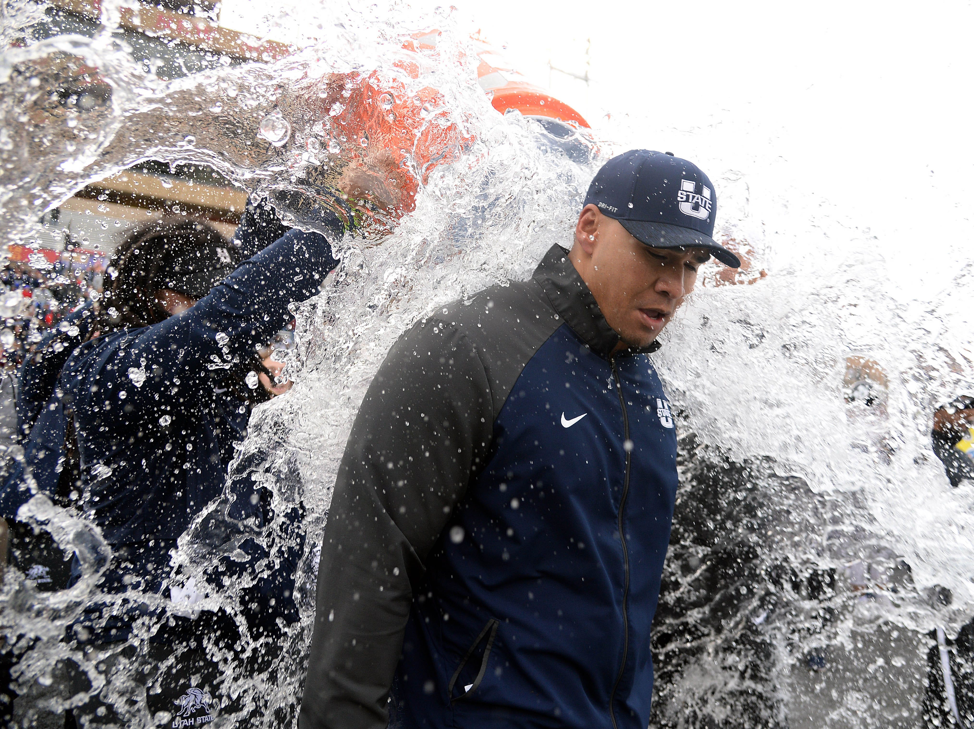 Utah State Aggies interim coach Frank Maile is doused after beating the North Texas Mean Green in the New Mexico Bowl.